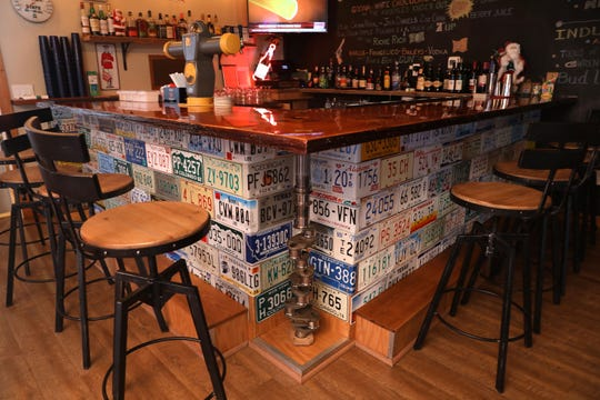 The bar, constructed of license plates, a crankshaft, and an old cedar telephone pole, at Knuckles Incorporated in Stony Point Nov. 26, 2018.