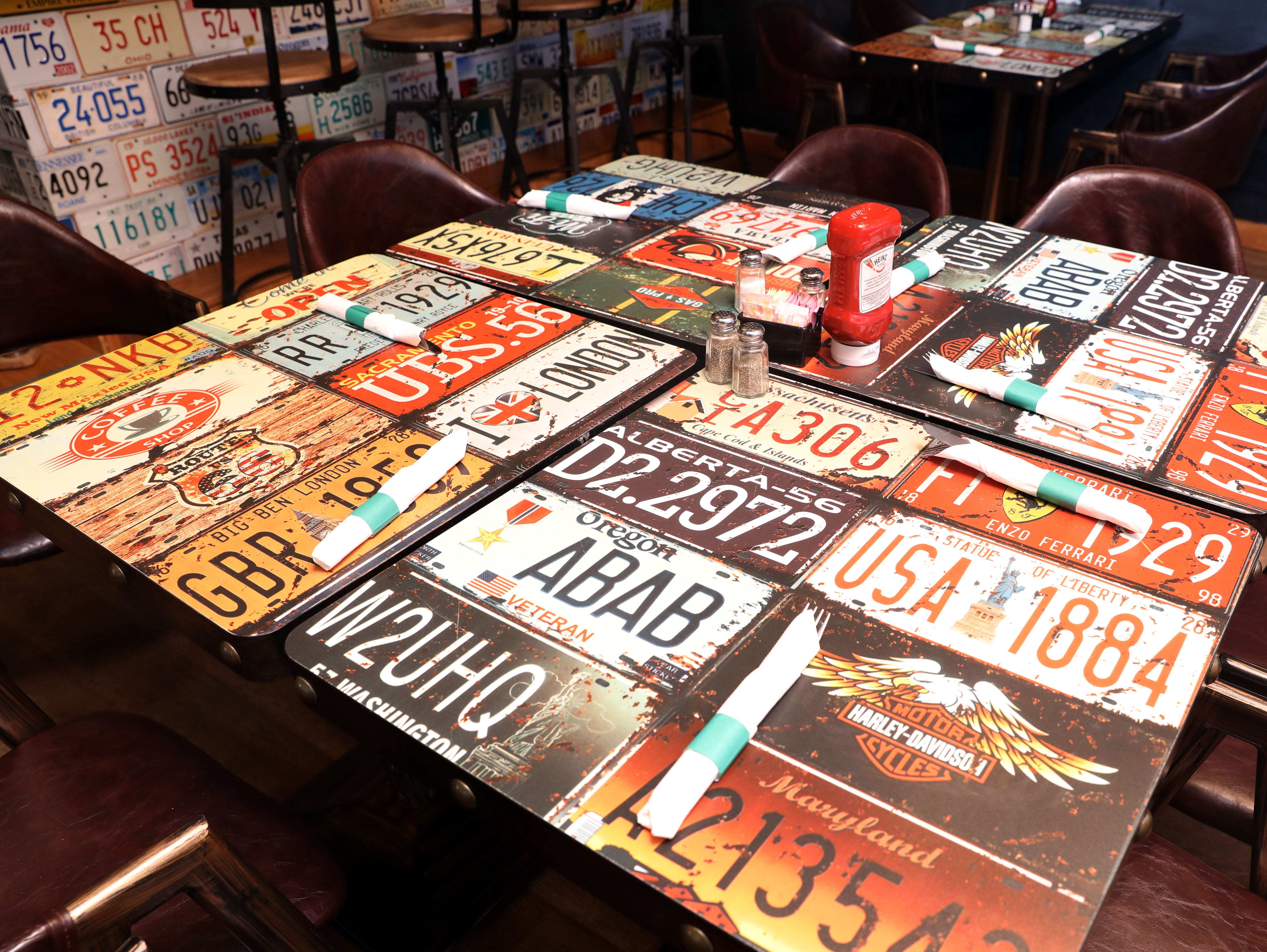 License plates cover the tables at Knuckles Incorporated, a new restaurant in Stony Point, Nov. 26, 2018.