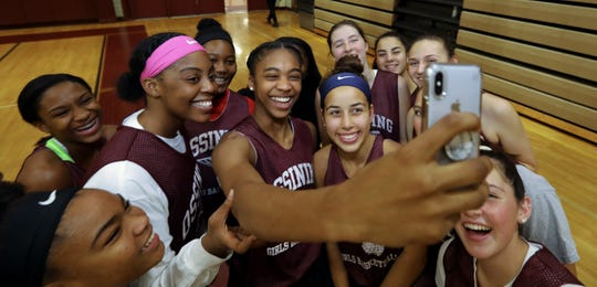 Ossining High School basketball players look at their phones before a basketball practice at the school Nov. 26, 2018.