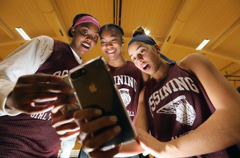 Kailah Harris, left, Aubrey Griffin and Jaida Strippoli look at their phones before a basketball practice at Ossining High School Nov. 26, 2018.