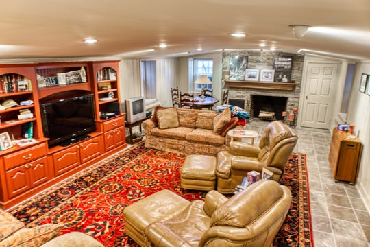 The lower-level family room at 2 Alapocas Drive has a stone fireplace.