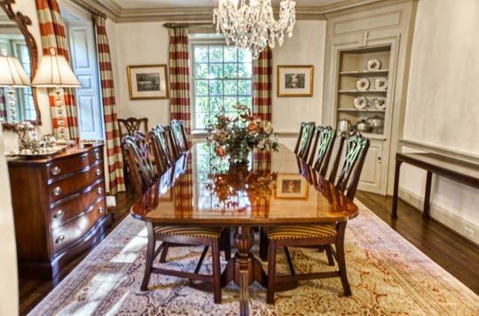 A formal dining room at 2 Alapocas Drive features millwork and a built-in china closet.