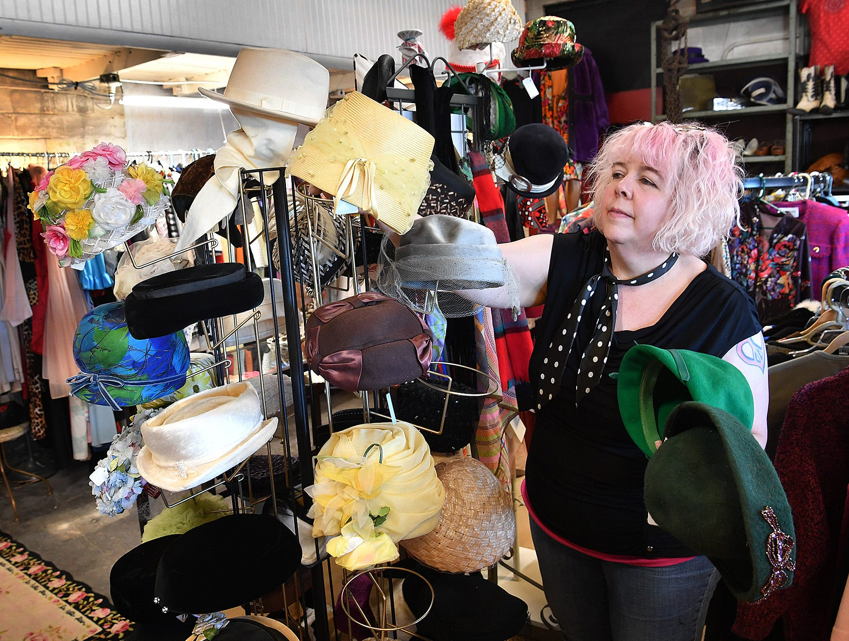 Janet Ehling of Fashion Garage sets up a display of vintage hats at her new store located at the former Gragg Motor Company on Lamar.