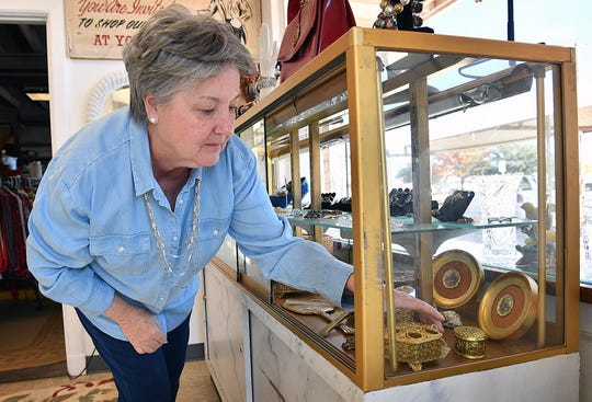 Connie Bennett straightens up a display in a jewelry case at Fashion Garage, a new boutique selling vintage, retro and contemporary fashions for men and women.