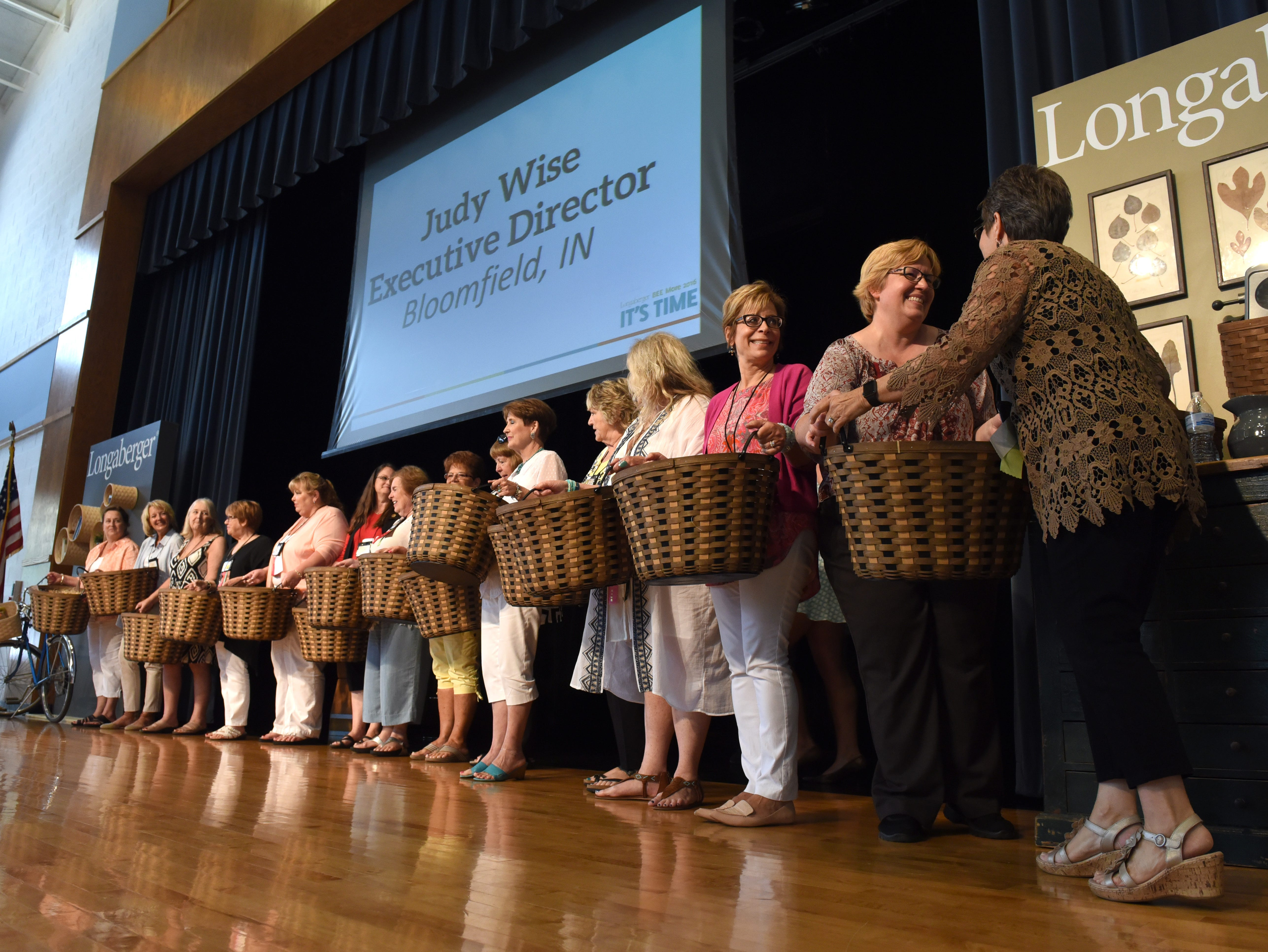 Longaberger consultants are given honorary baskets for becoming company directors during the Longerberger Bee at Tri-Valley High School.