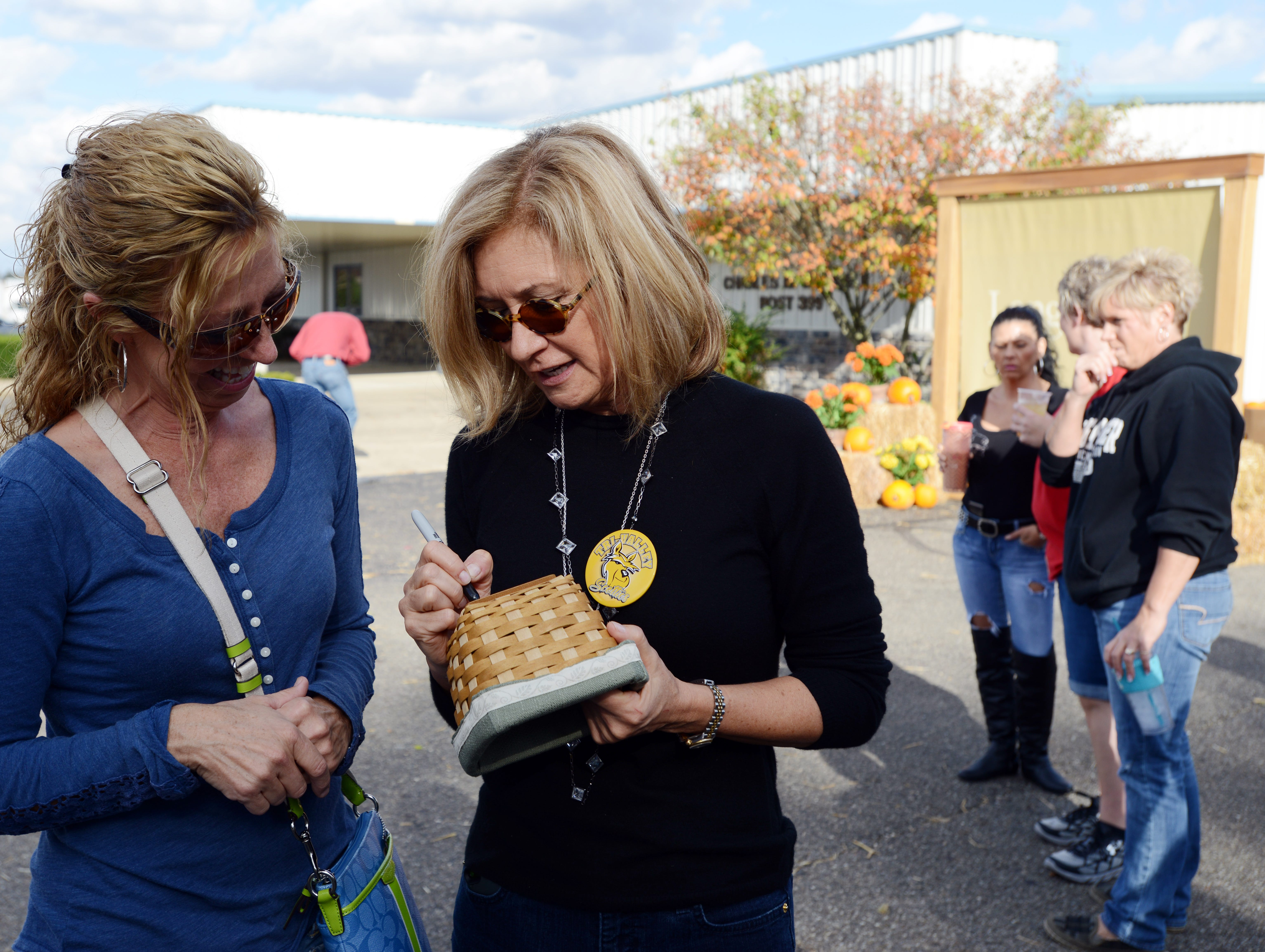 Tammy Longaberger signs a basket for a long-time associate during an event in Dresden.