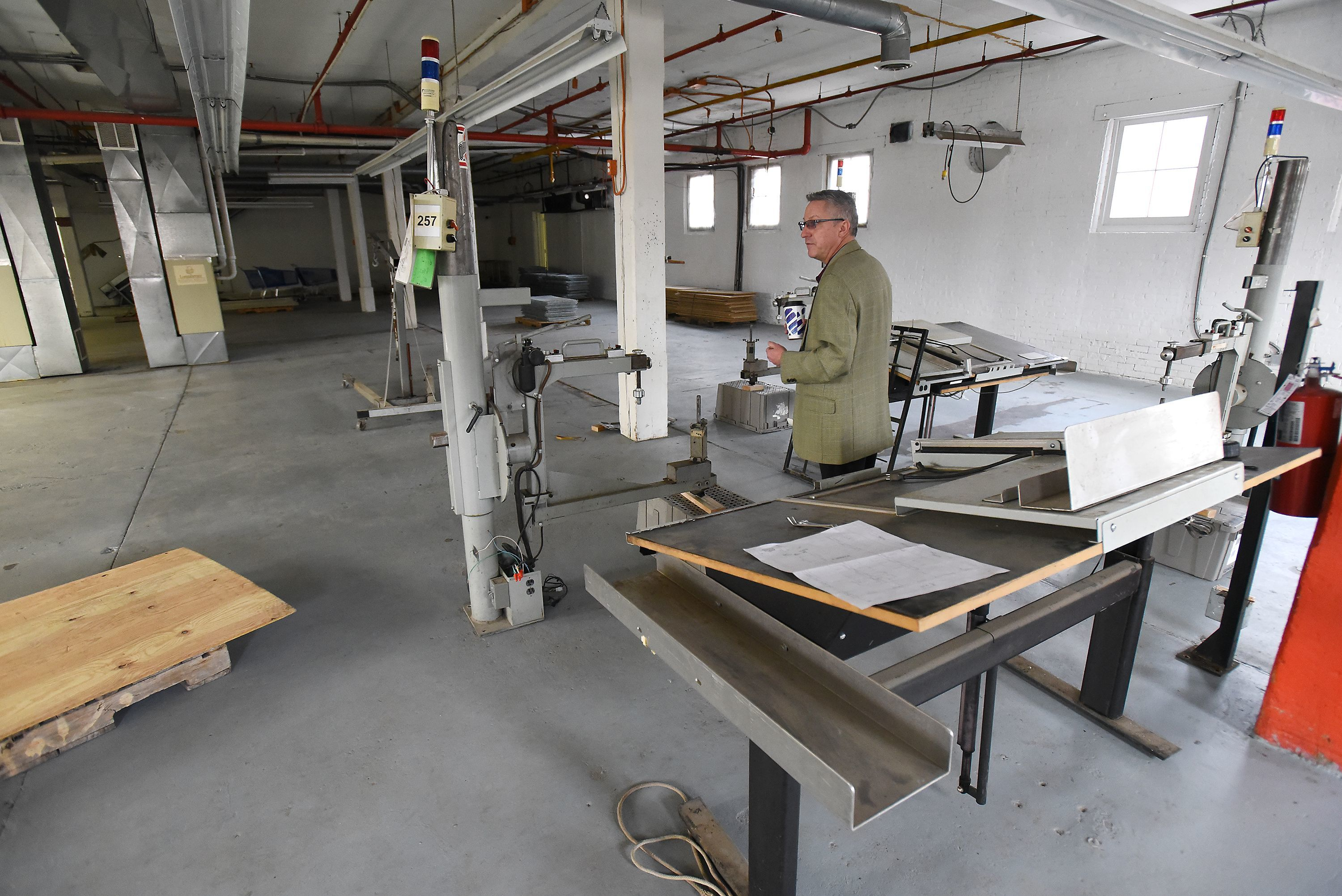 Brenton Baker, President for Marketing, Communications and Events for Longaberger's parent company JRJR Networks, looks at the company's new manufacturing facility in Dresden while equipment is being installed.