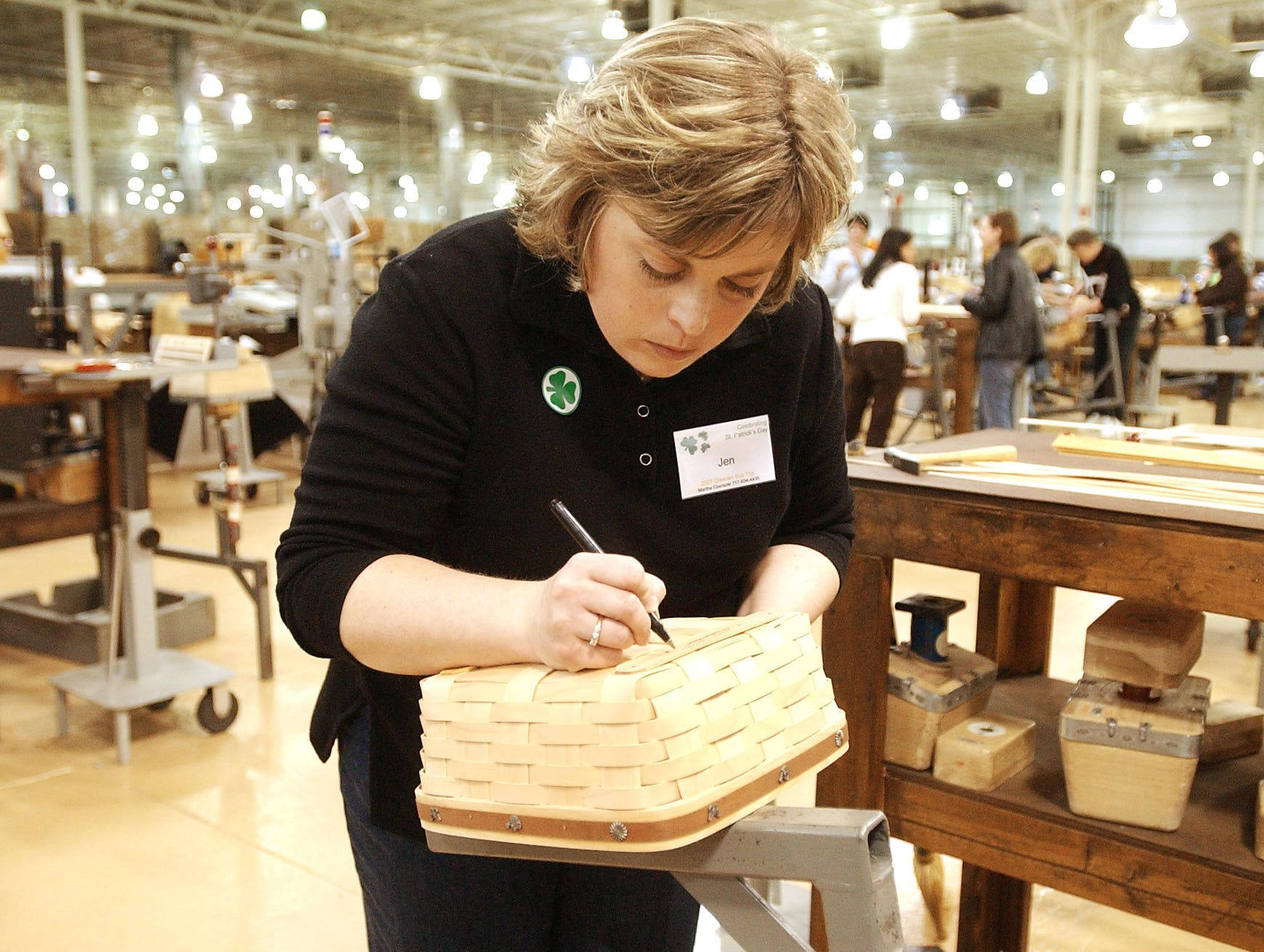 Jennifer Kiner, of Newville, PA. signs her basket, a Longaberger tradition, during the Seasonal Make A Basket at the Longerberger Homestead's Homestead Madness event in Frazeysburg in 2007.