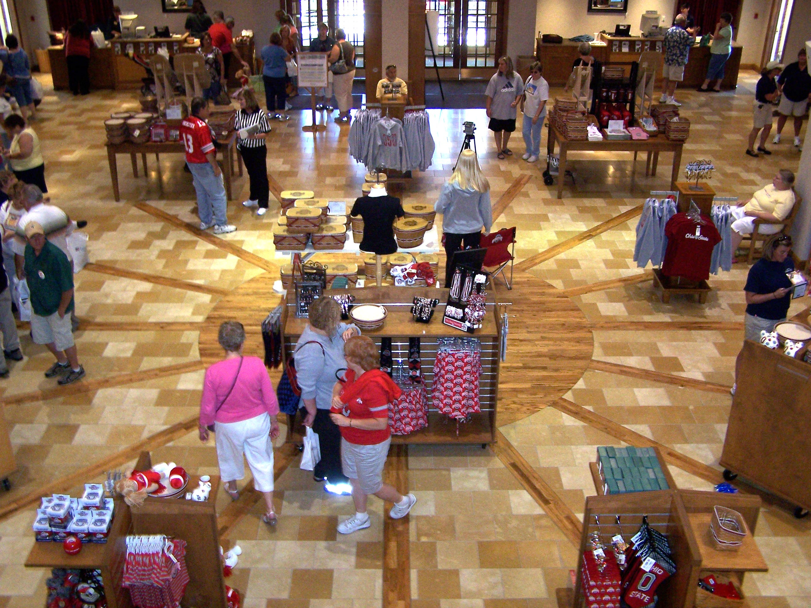 Shoppers browse the new collegiate baskets in the foyer of the Longaberger Homestead Friday during Heritage Days.