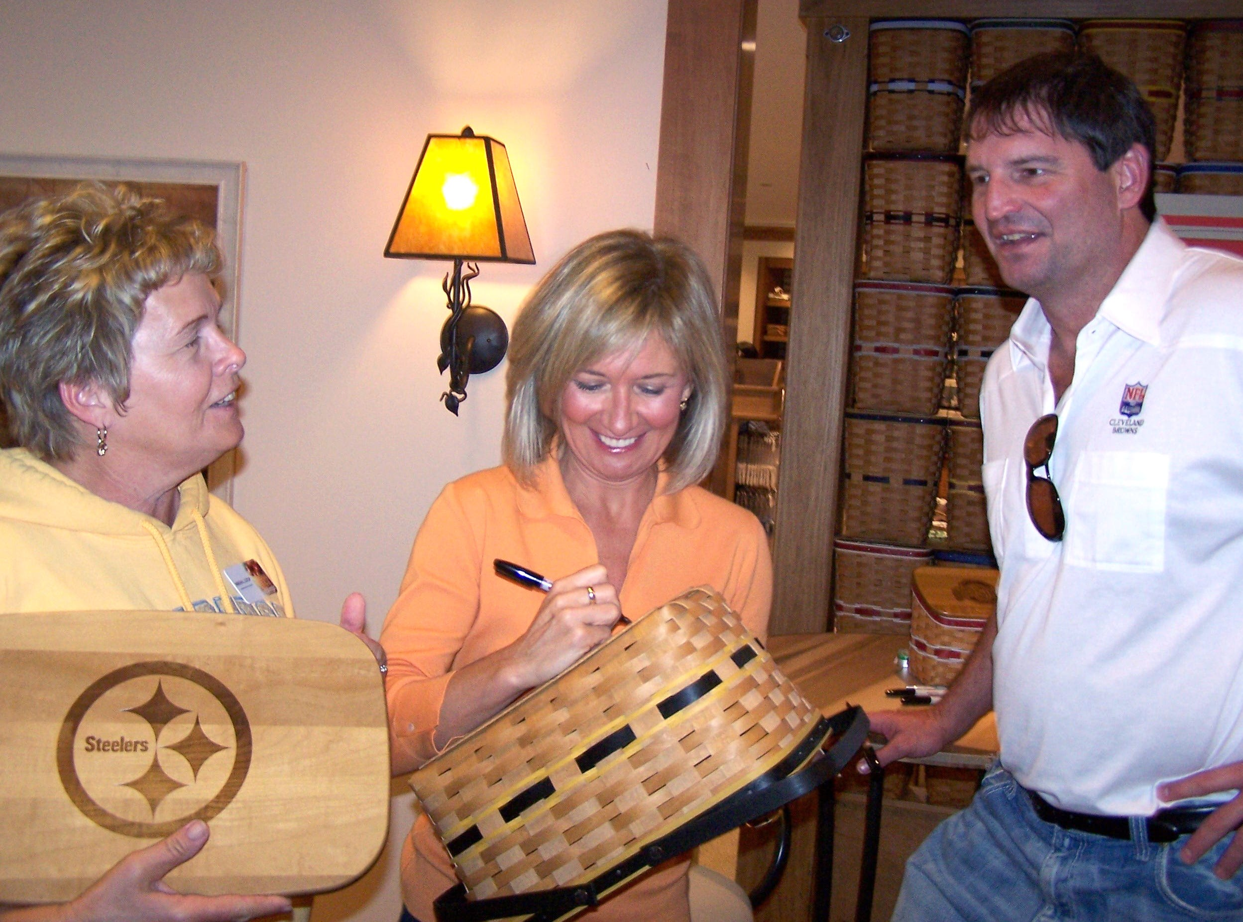 Bernie Kosar chats with Marsha Cutlip as Tami Longaberger signs Team Spirit basket lids at the Longaberger Heritage Days event Friday.
