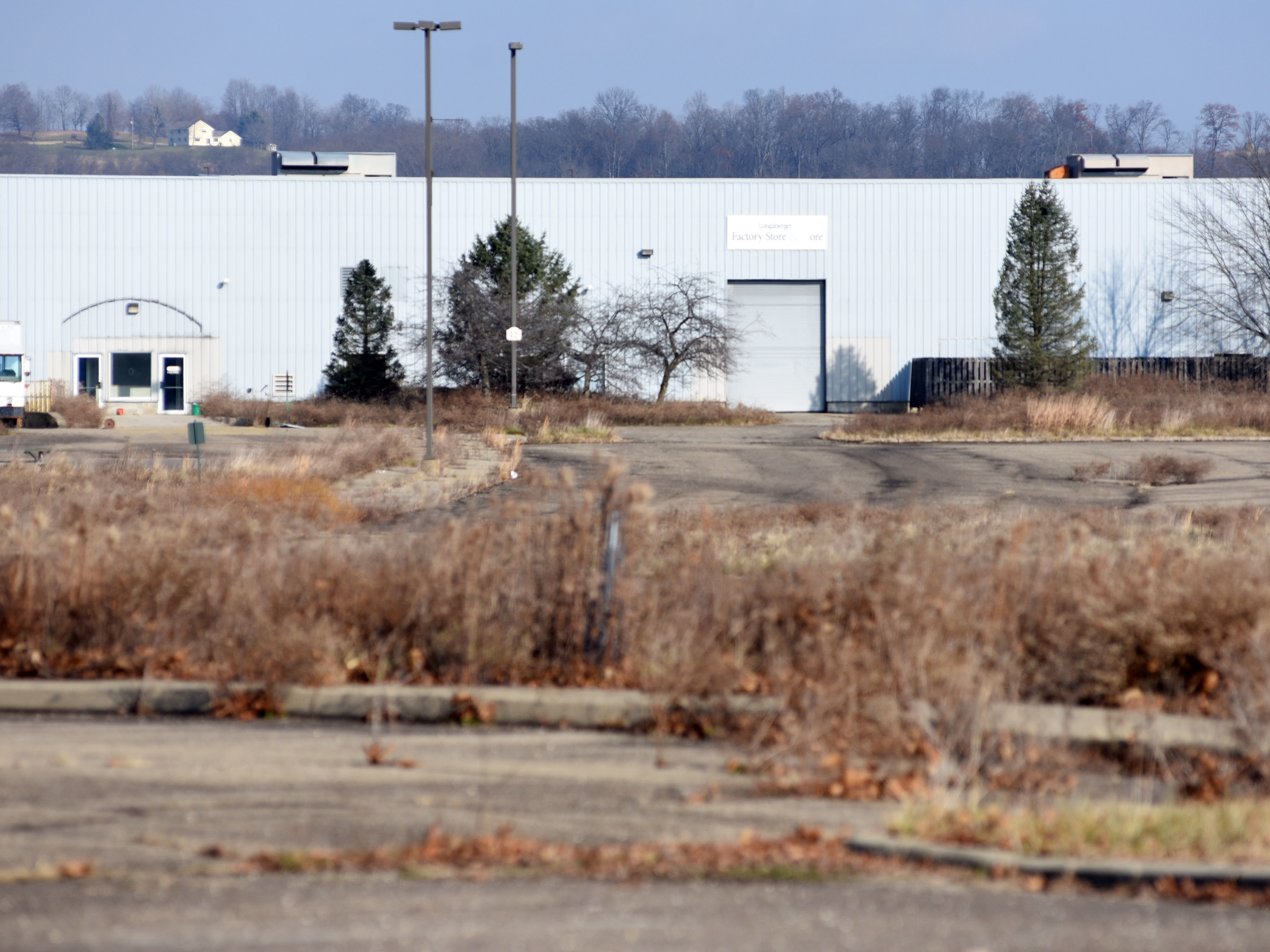 A weedy parking lot stands next to one of the Longaberger buildings recently sold to MPI Group, a mattress manufacturer.