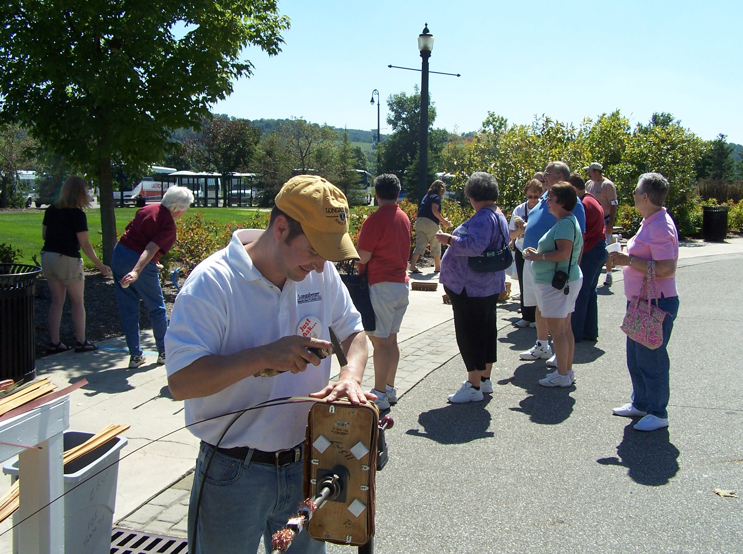 17 year Longaberger employee, Craig Wilcox, weaves one of the six special edition bread baskets as a line forms behind him for the bread basket toss game at Friday's Heritage Days event at the Longaberger Homestead.