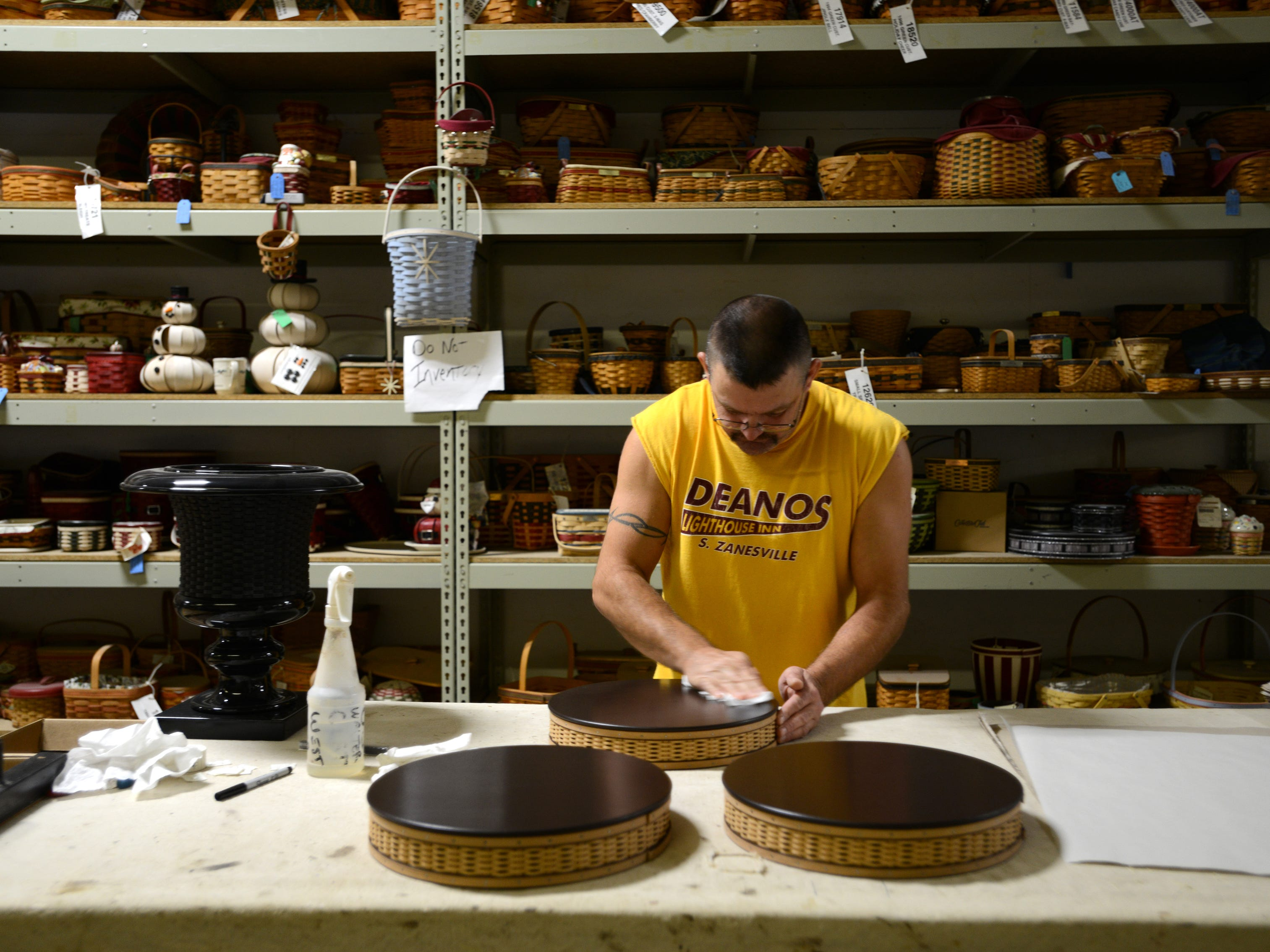 Mark Beach polishes the wooden lid of a Serenity basket in Longaberger's Master's Studio line.