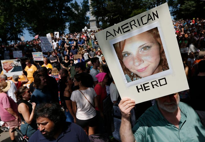 """A counter-protester holds a photo of Heather Heyer on Boston Common at a """"Free Speech"""" rally organized by conservative activists, in Boston on Aug. 19, 2017."""
