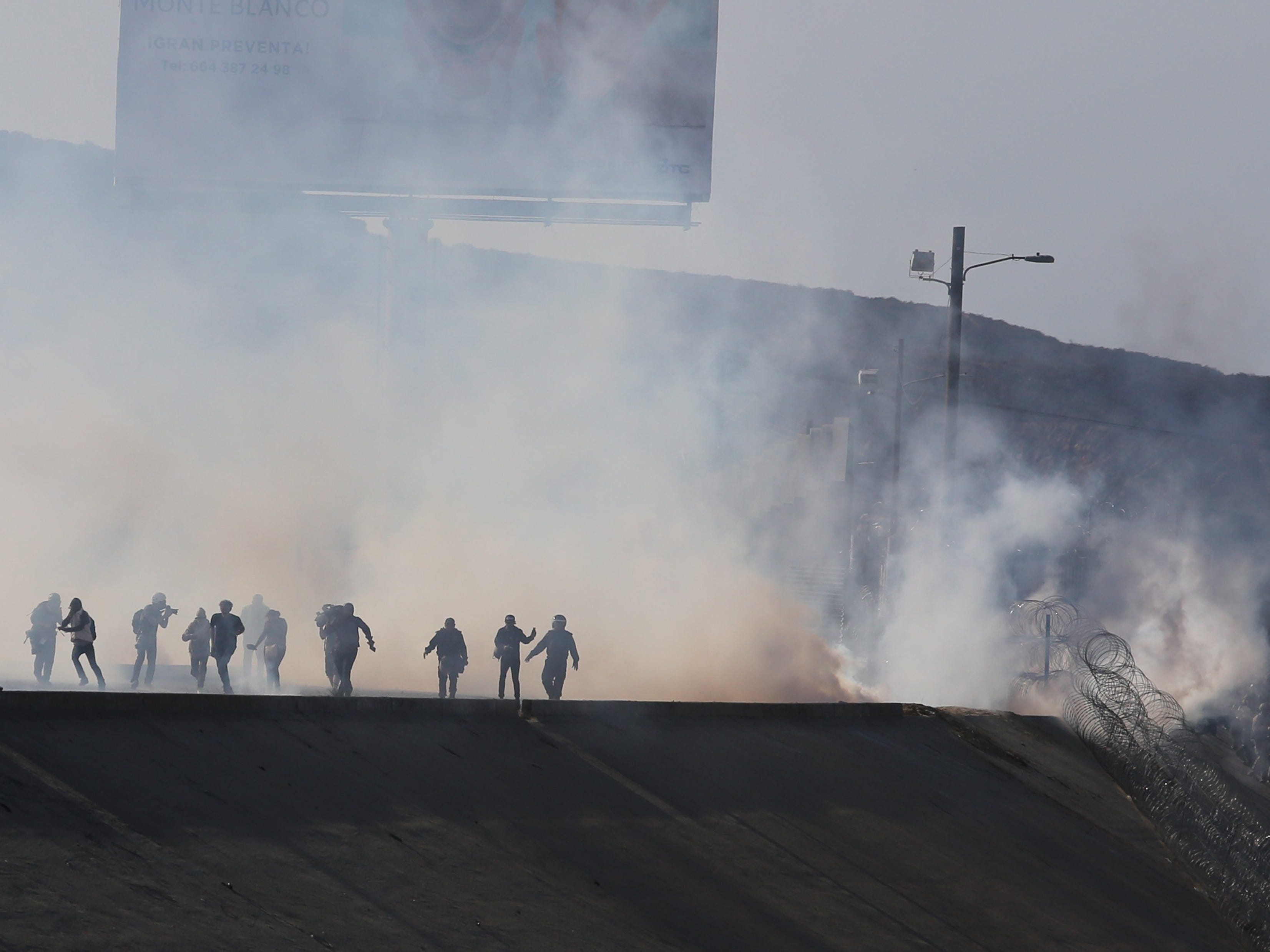 Tear gas is used by border police to prevent groups of people from crossing El Chaparral, in Tijuana, Mexico, Nov. 25, 2018. A group of migrants from the caravan of Central Americans who advanced towards the San Ysidro gateway deviated from the planned route to try to cross the border wall by other points.