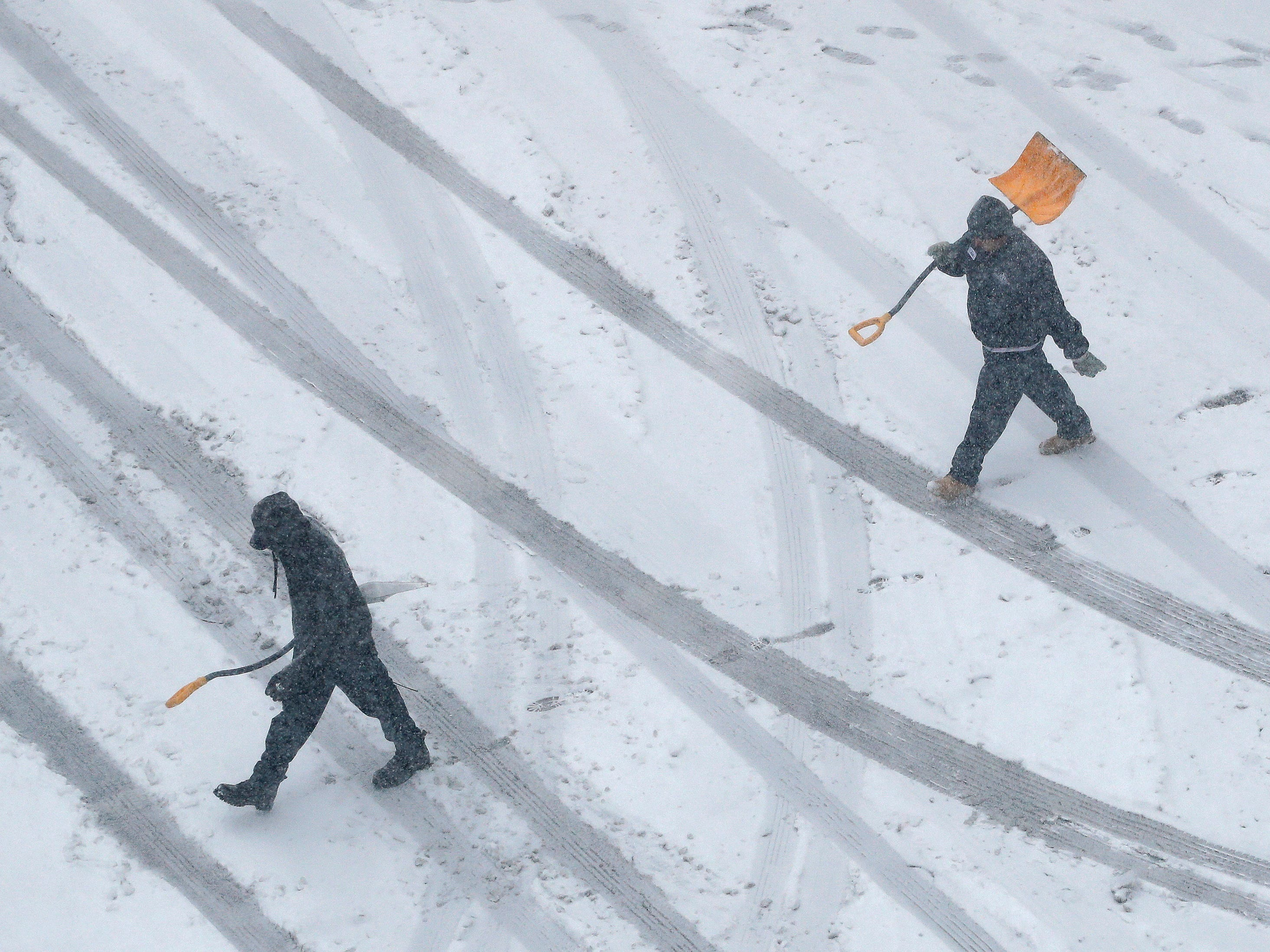 Workers carry snow shovels as snow falls on Nov. 25, 2018, in downtown Kansas City, Mo.