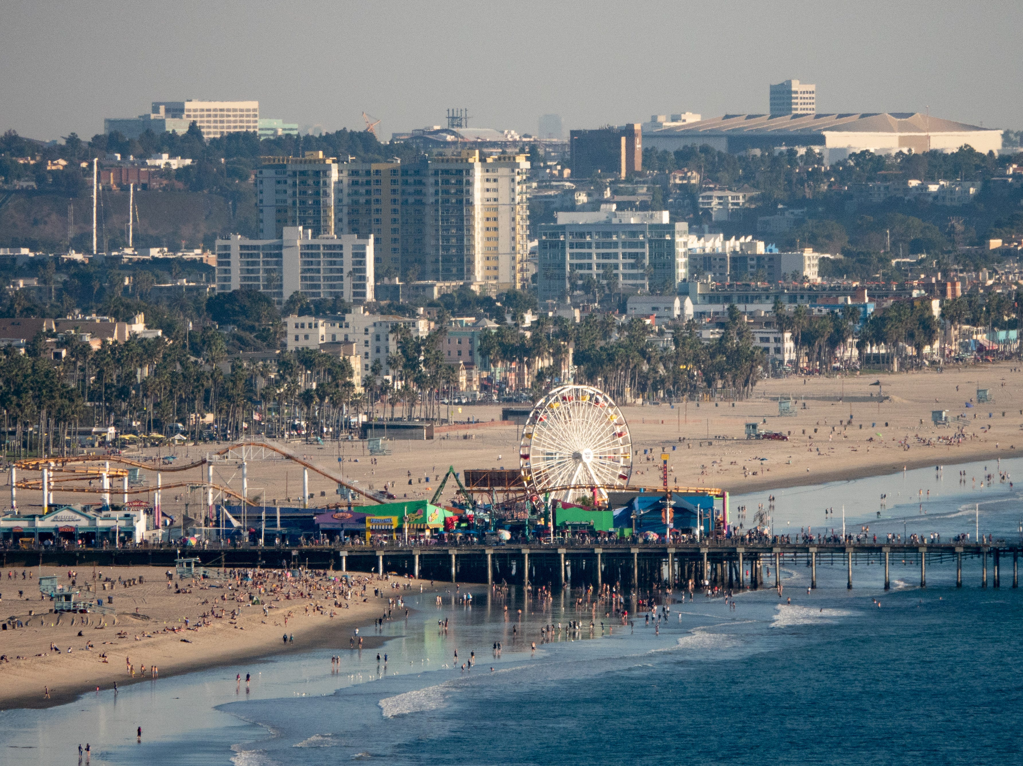 An overhead shot of the Santa Monica Pier and Pacific Park from nearby Pacific Palisades