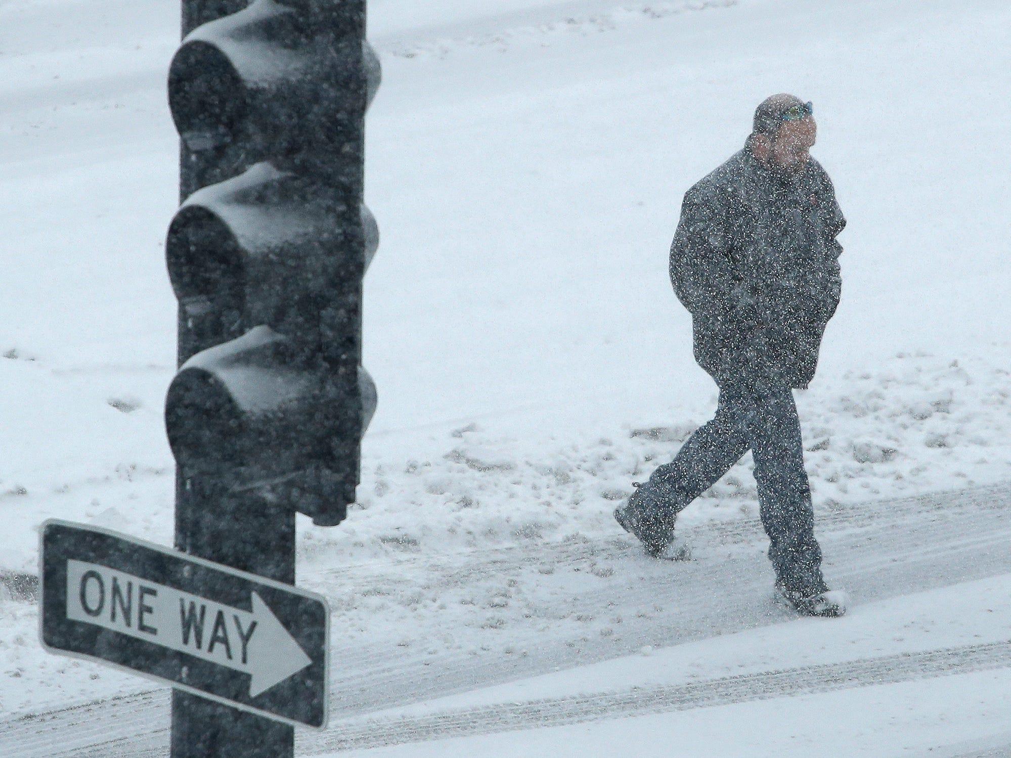 A pedestrian walks as snow falls on Nov. 25, 2018, in downtown Kansas City, Mo.