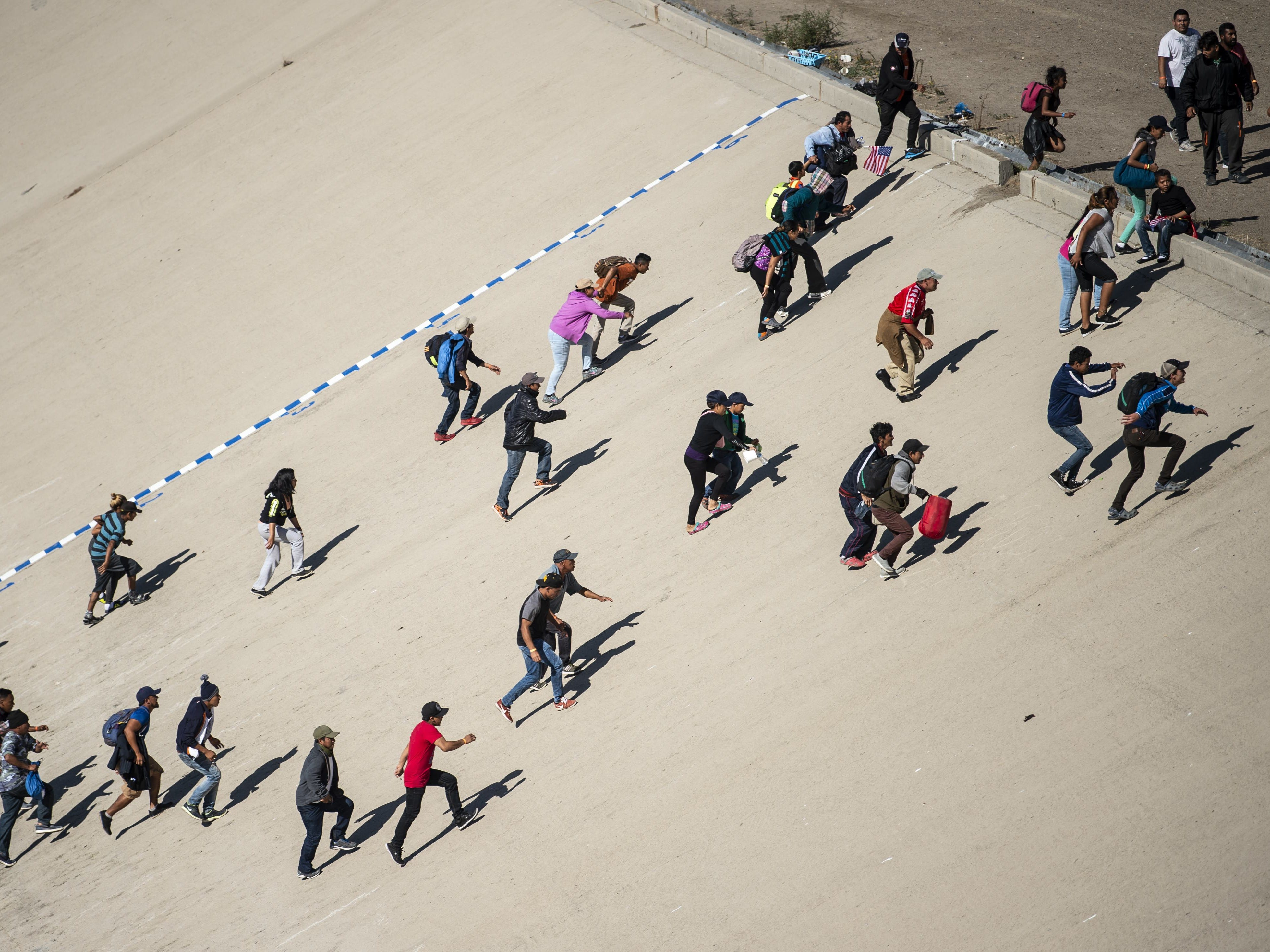 A group of Central American migrants cross the almost dry riverbed of the Tijuana River in an attempt to get to El Chaparral port of entry, in Tijuana, Baja California State, Mexico, near US-Mexico border on Nov. 25, 2018. .