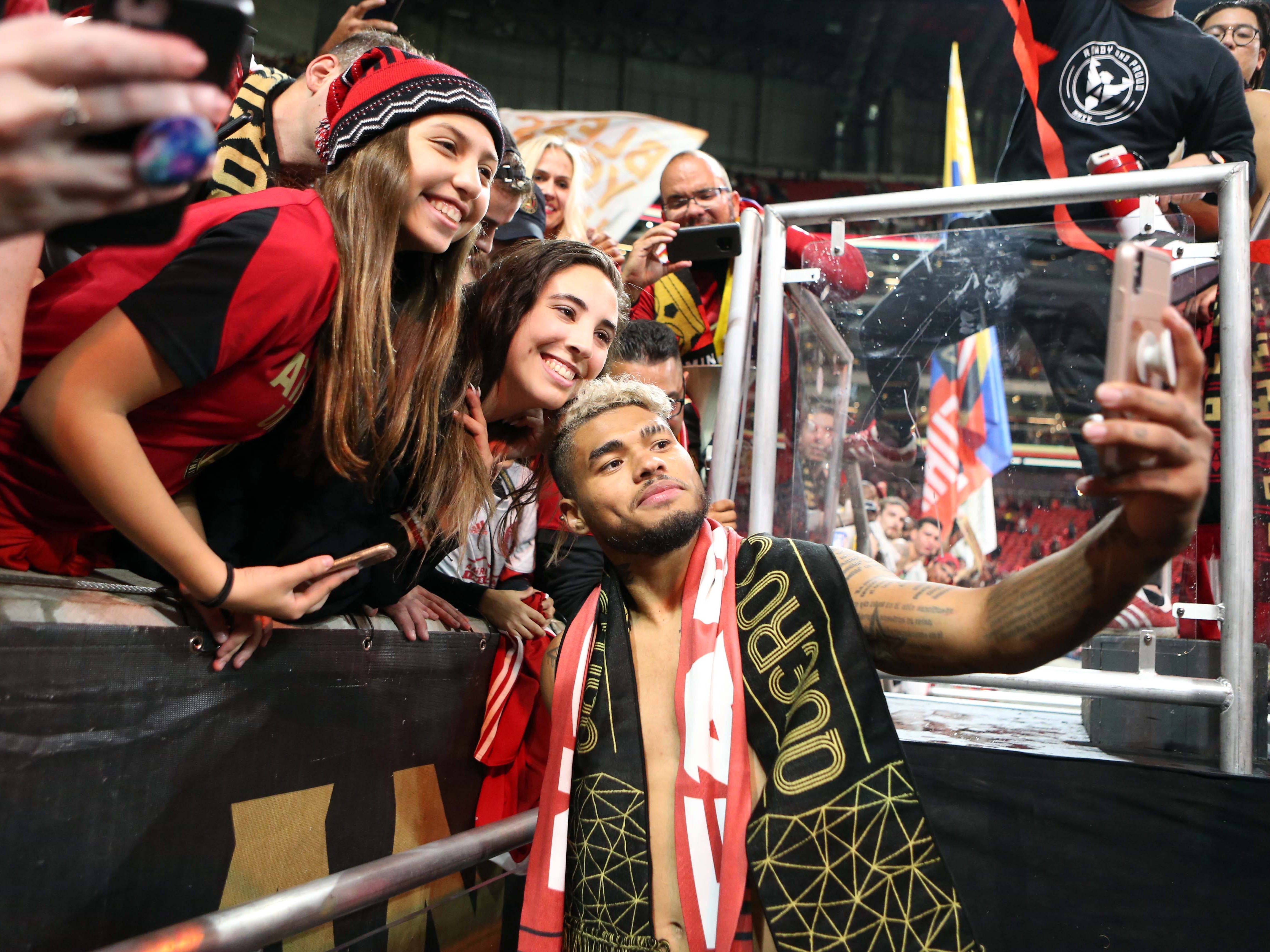 Atlanta United forward Josef Martinez takes a photo with fans after defeating the New York Red Bulls in the first leg of the MLS Eastern Conference Championship at Mercedes-Benz Stadium.