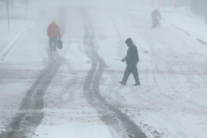 Pedestrians walk along a snow-covered street Sunday, Nov. 25, 2018, in Kansas City, Mo. Blizzard-like conditions have closed highways and delayed air travel as a winter storm moves through the Midwest. (AP Photo/Charlie Riedel) ORG XMIT: MOCR108