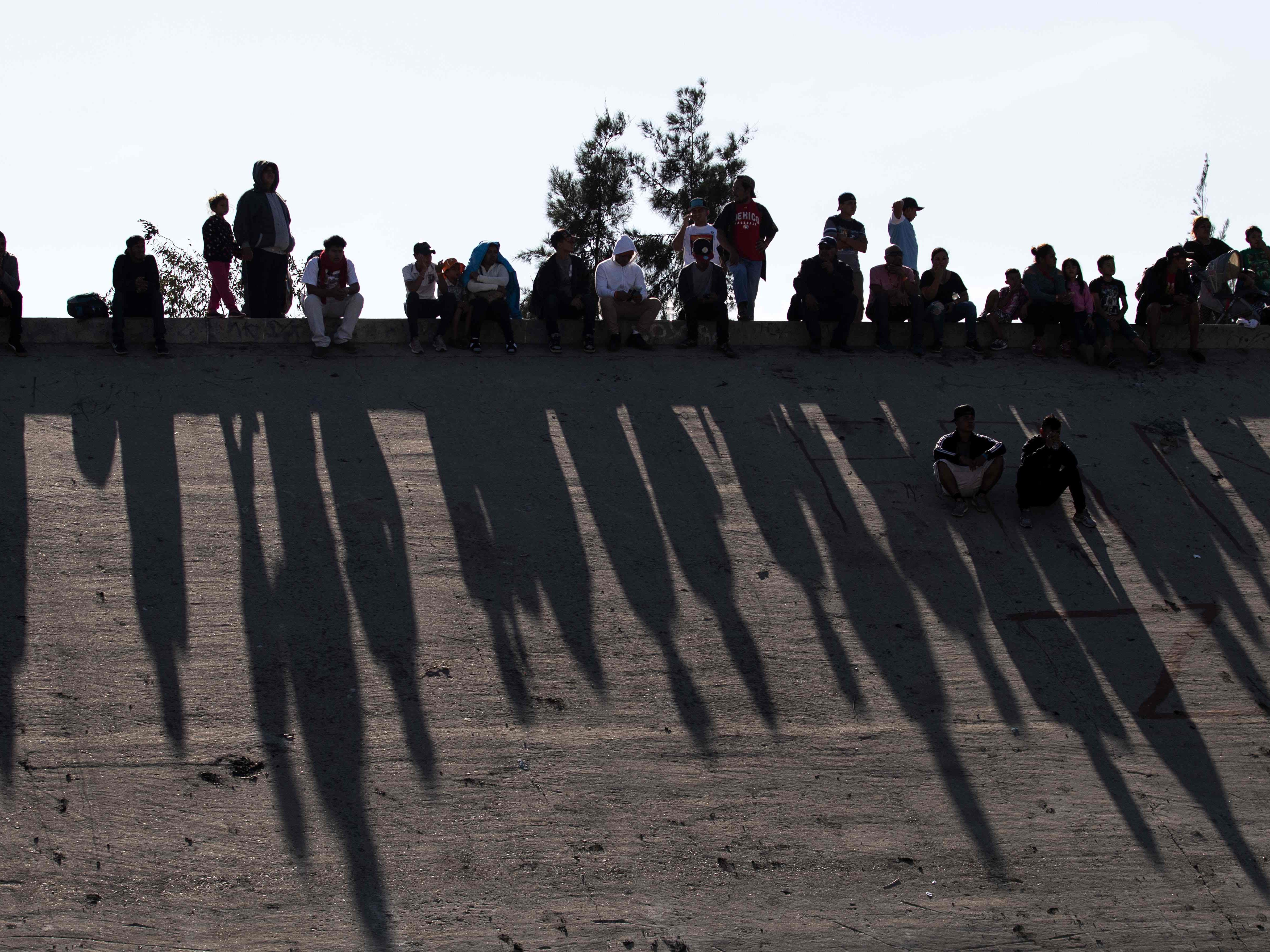 Central American migrants sit along the concrete waterway of the bordering Tijuana River right across the El Chaparral border crossing point in Tijuana, Mexico, on Nov. 25, 2018.