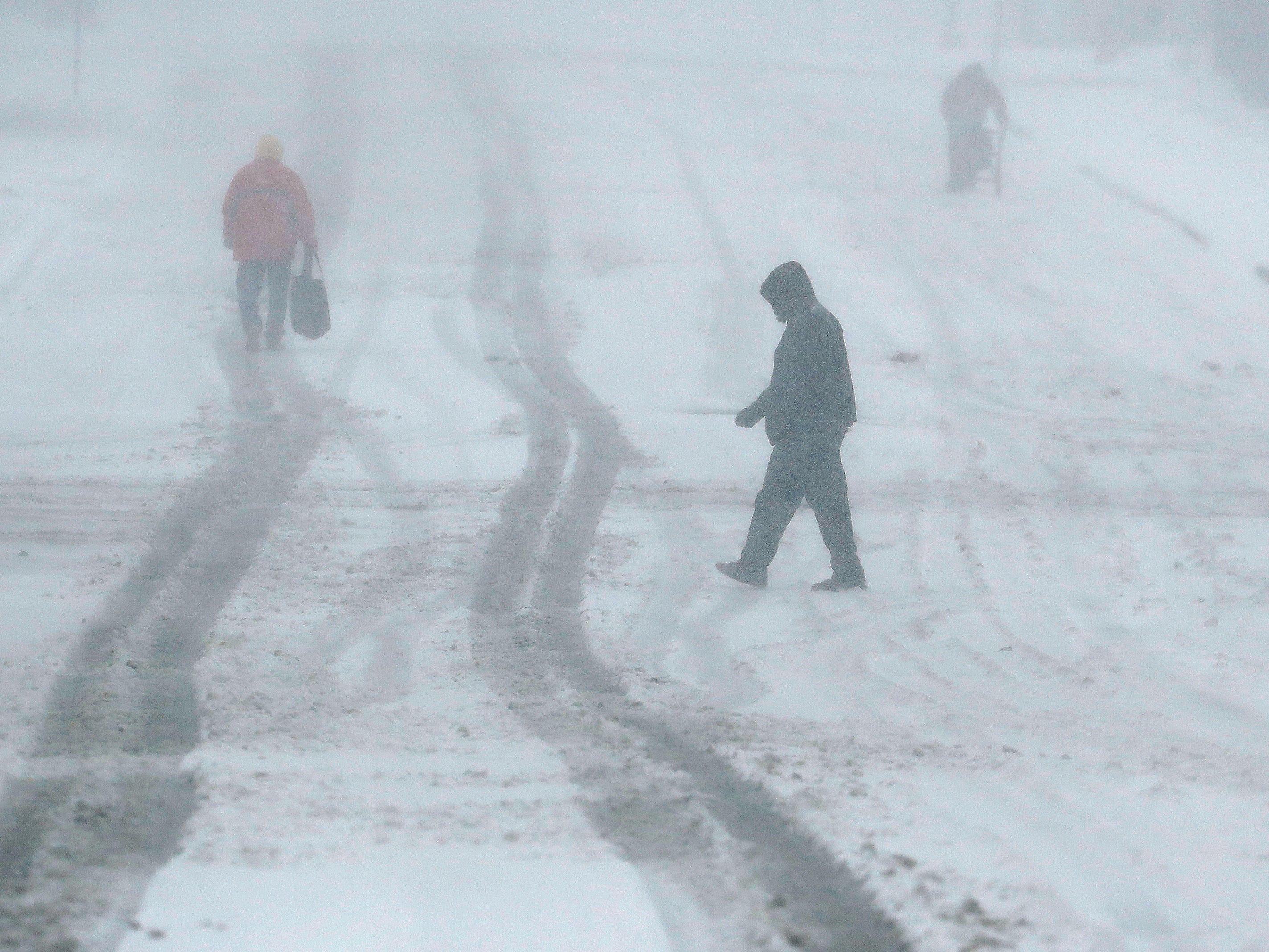 Pedestrians walk along a snow-covered street on Nov. 25, 2018, in Kansas City, Mo.