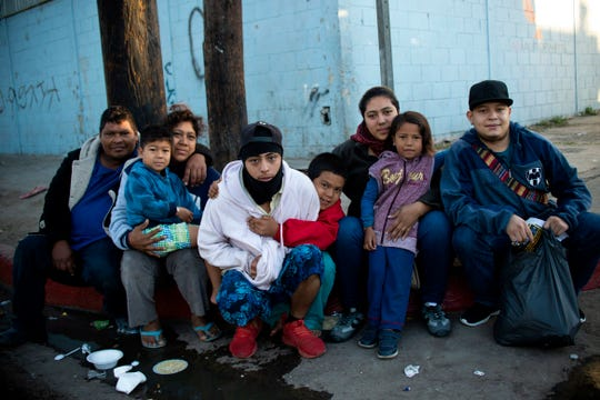 A family from Honduras poses for a picture outside a temporary shelter in Tijuana, Baja California State, Mexico, near the U.S.-Mexico border on November 26, 2018.