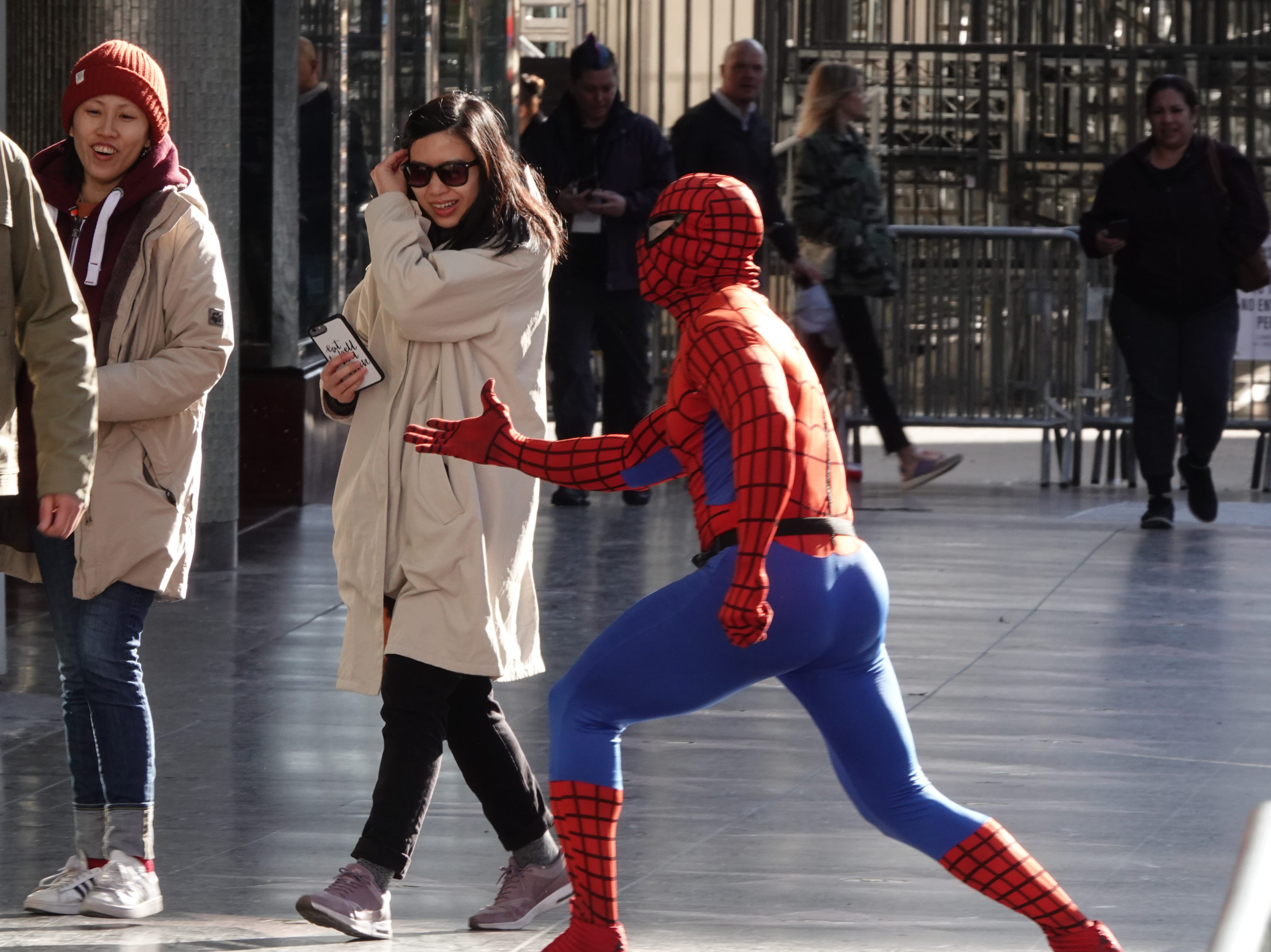 A costumed Spiderman performer tries to stop action on Hollywood Blvd.