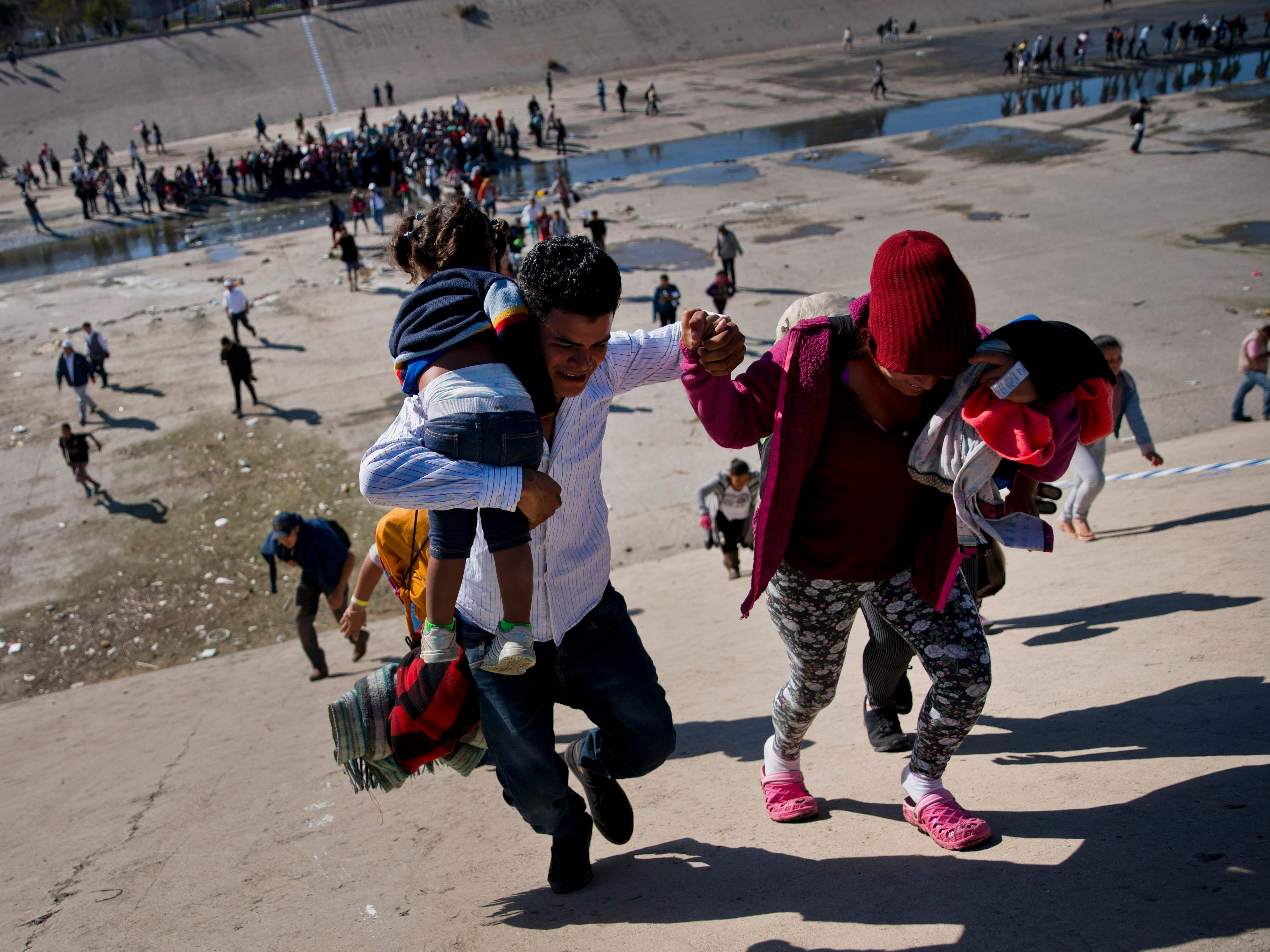 Migrants walk up a riverbank at the Mexico-U.S. border after pushing past a line of Mexican police at the Chaparral border crossing in Tijuana, Mexico, on Nov. 25, 2018, as they try to reach the U.S.