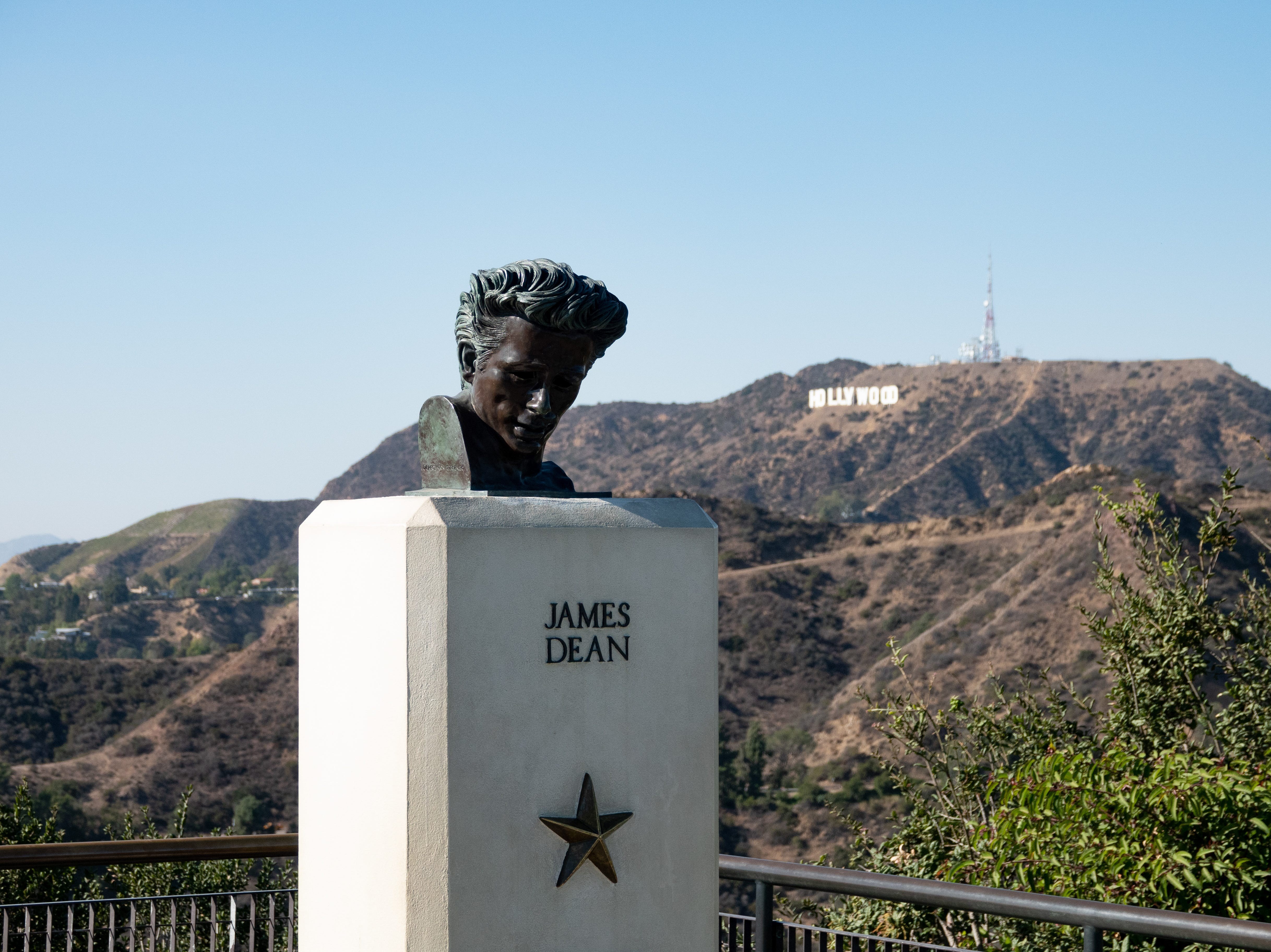 """The film """"Rebel without a Cause"""" was partially filmed at Griffith Observatory. A bust to honor the late actor James Dean is at the observatory, with the iconic Hollywood sign in the background."""