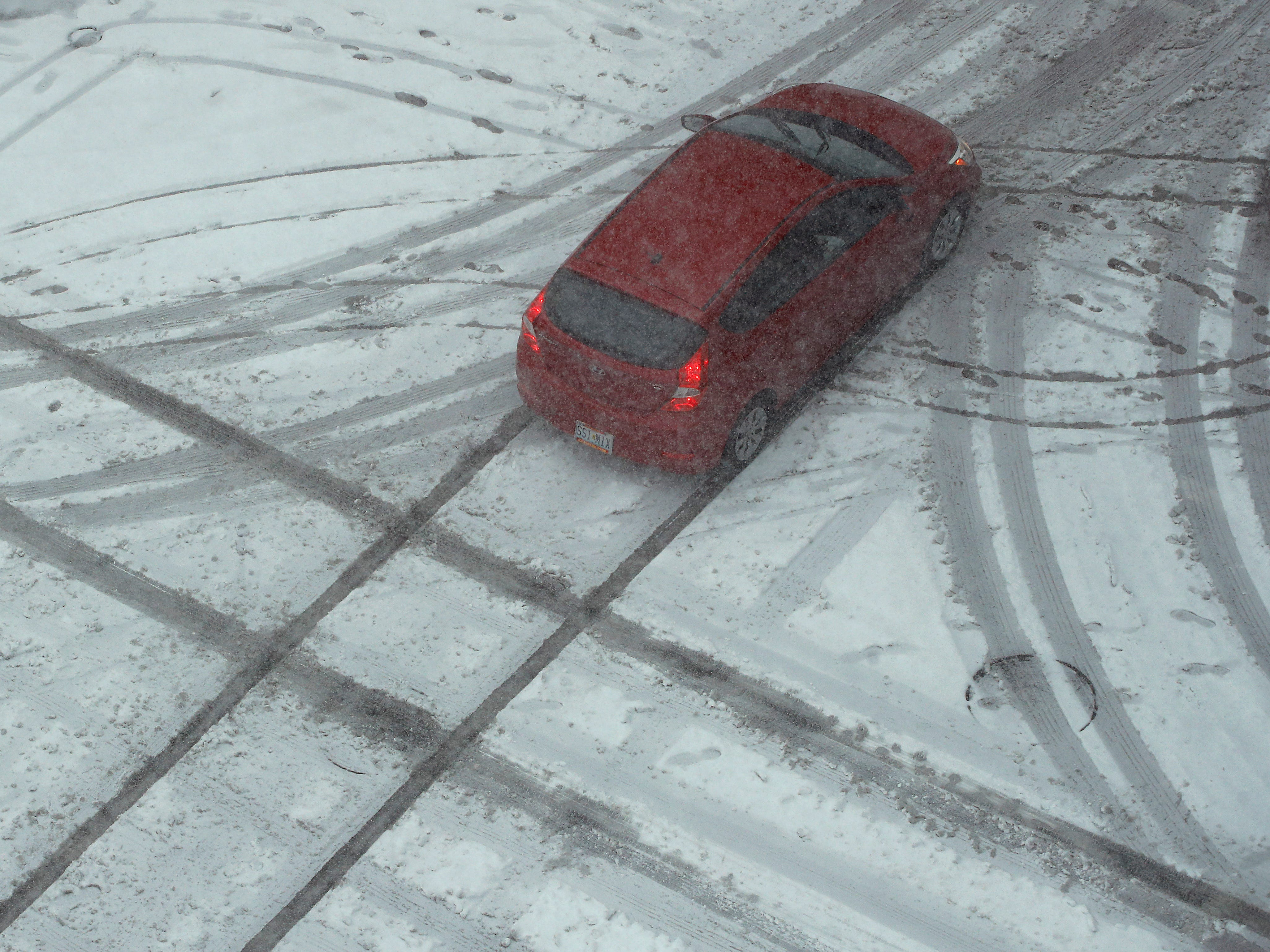 A motorist drives though a slick intersection as snow falls on Nov. 25, 2018, in downtown Kansas City, Mo.