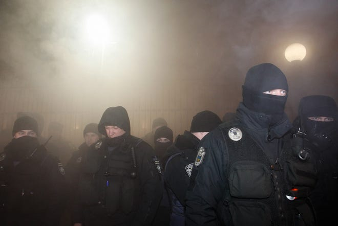 Ukrainian policemen guard the Russian embassy building with smoke behind during Ukrainian activists rally in Kiev, Ukraine, on November 25, 2018.