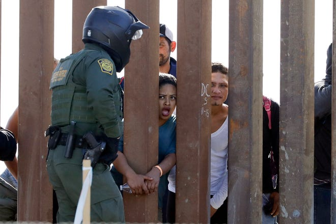 Migrants from Central America yell through a border wall at a U.S. Border Patrol agent after he pulled down a banner on Nov. 25, 2018, in San Diego.