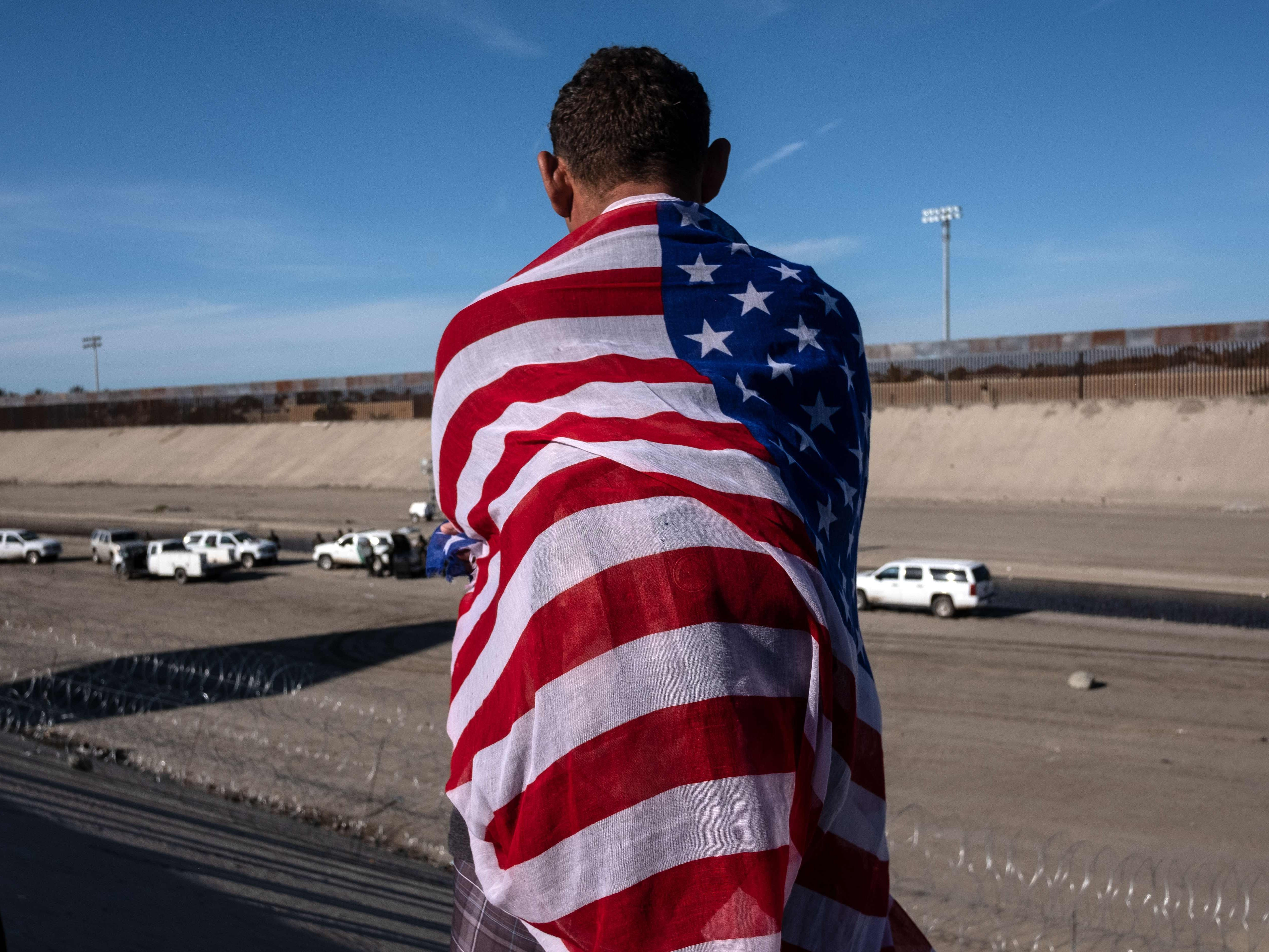 A Central American migrant wrapped in a U.S. flag looks at the almost dry riverbed of the Tijuana River near the El Chaparral border crossing near U.S.-Mexico border in Tijuana, Mexico, on Nov. 25, 2018.