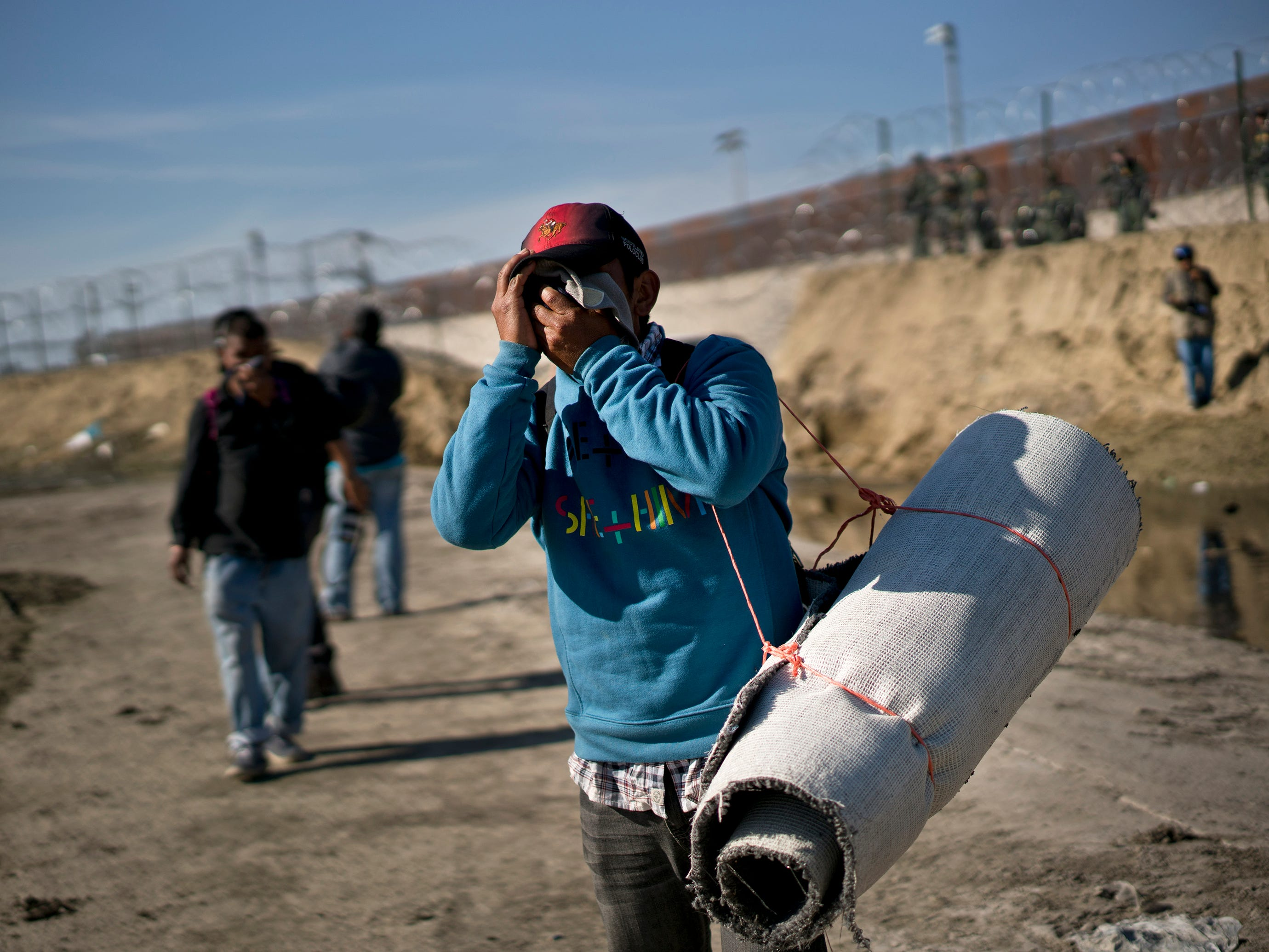A migrant wipes his face after U.S. border agents fired tear gas at a group of migrants who had pushed past Mexican police at the Chaparral border crossing in Tijuana, Mexico on Nov. 25, 2018.
