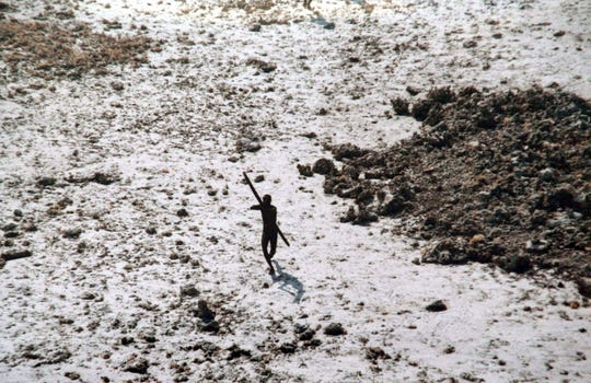 In this handout photo provided by the Indian Coast Guard and Survival International and taken in 2004, a man with the Sentinelese tribe aims his bow and arrow at an Indian Coast Guard helicopter as it flies over North Sentinel Island in the wake of the 2004 Indian Ocean tsunami.