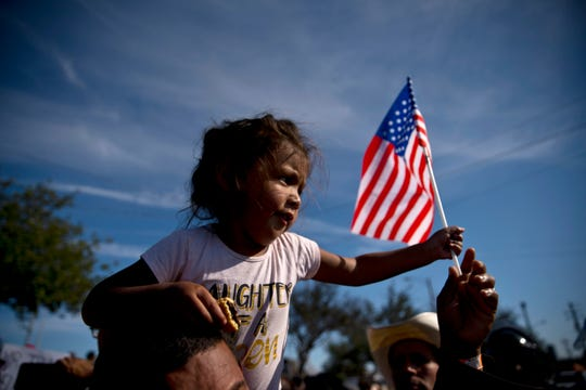 A migrant girl with a U.S. flag sits on the shoulders of a man marching with other migrants to the Chaparral border crossing in Tijuana, Mexico, Sunday, Nov. 25, 2018.