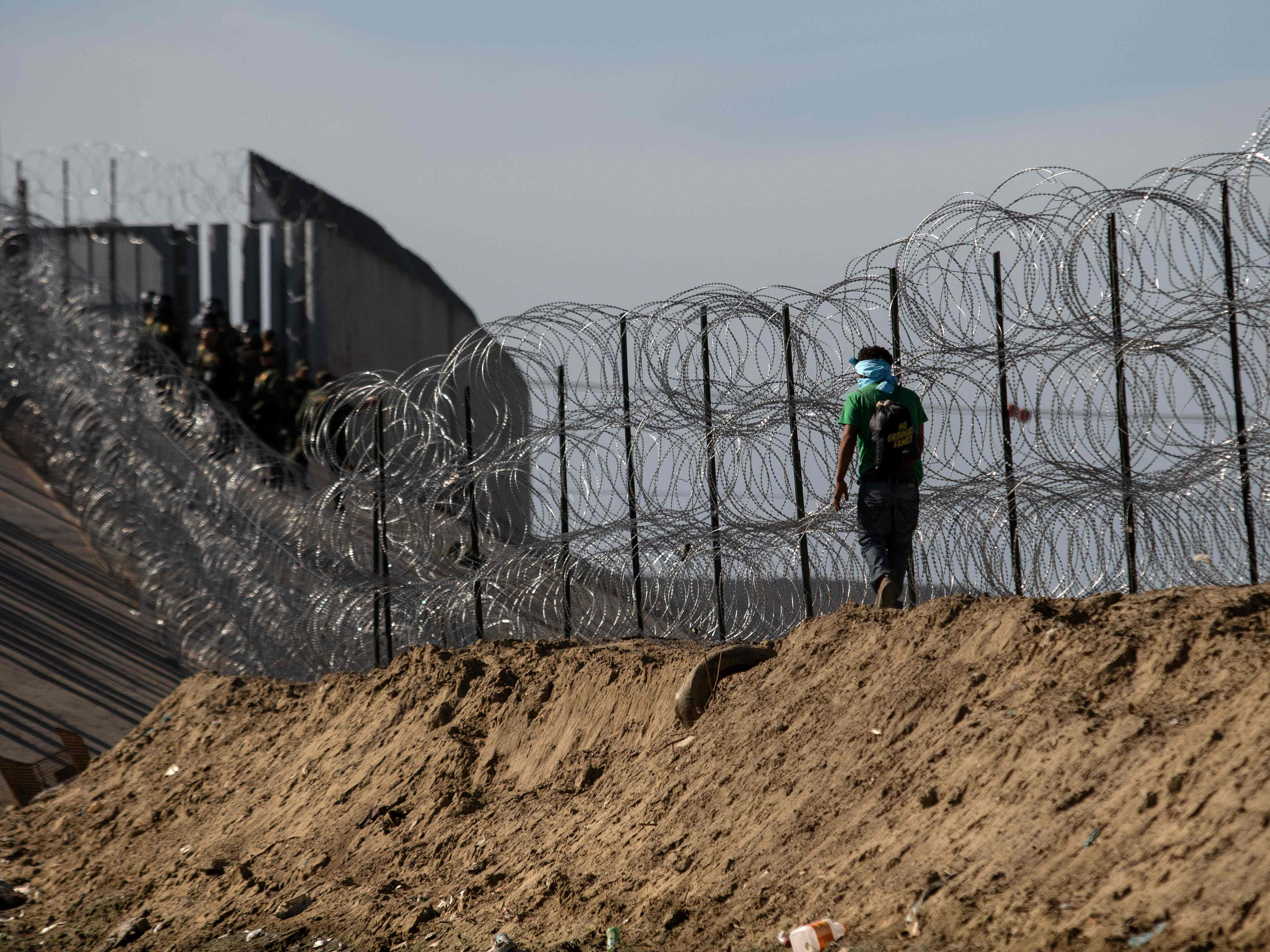 A man traveling with a caravan of Central American migrants walks along a barricade set by the U.S. Border Patrol along the Tijuana River, near the El Chaparral border crossing in Tijuana, Mexico, on Nov. 25, 2018.