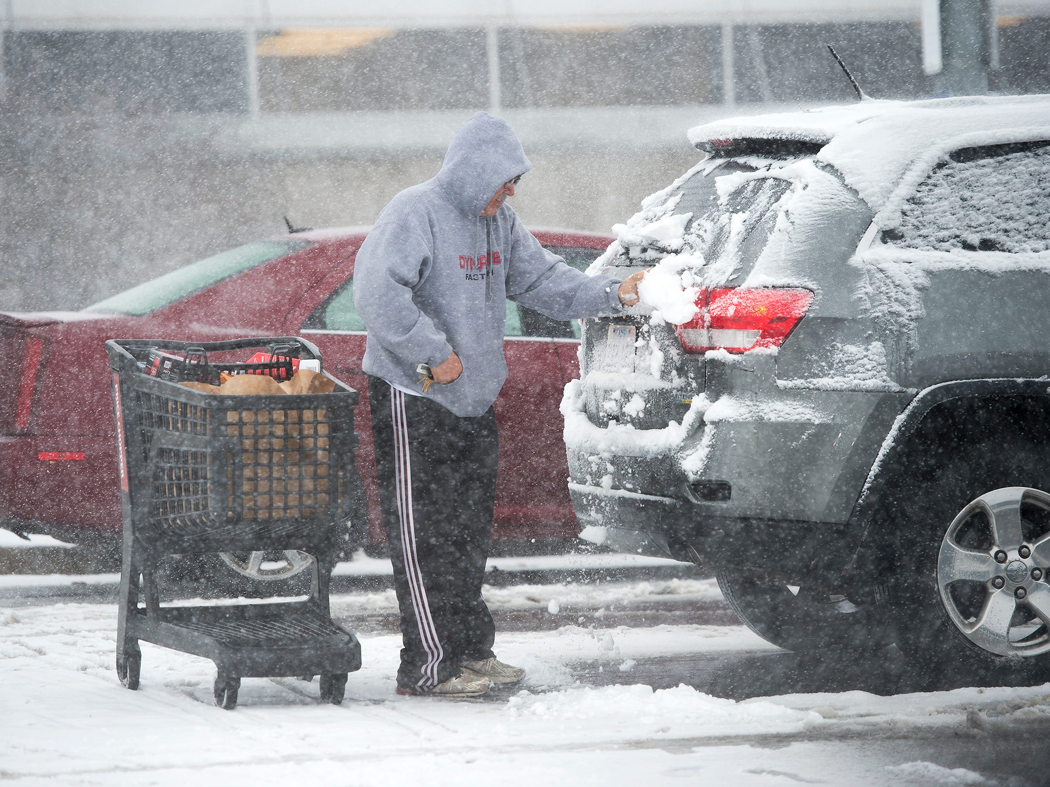 Anthony Walters of Mission, Kan., wipes snow from a vehicle before loading groceries into it on Nov. 25, 2018, in Roeland Park, Kan.