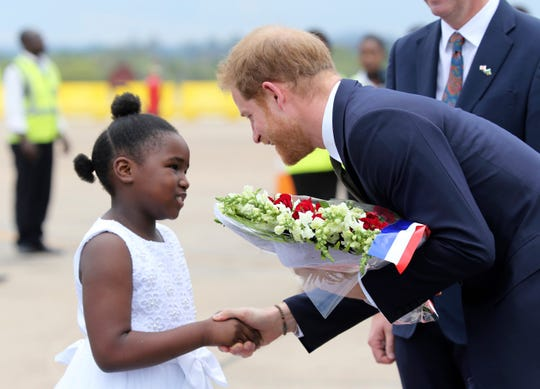 Prince Harry receives flowers from a girl upon his arrival at Kenneth Kaunda airport in Lusaka, Nov. 26, 2018, at the start of a two-day visit to Zambia