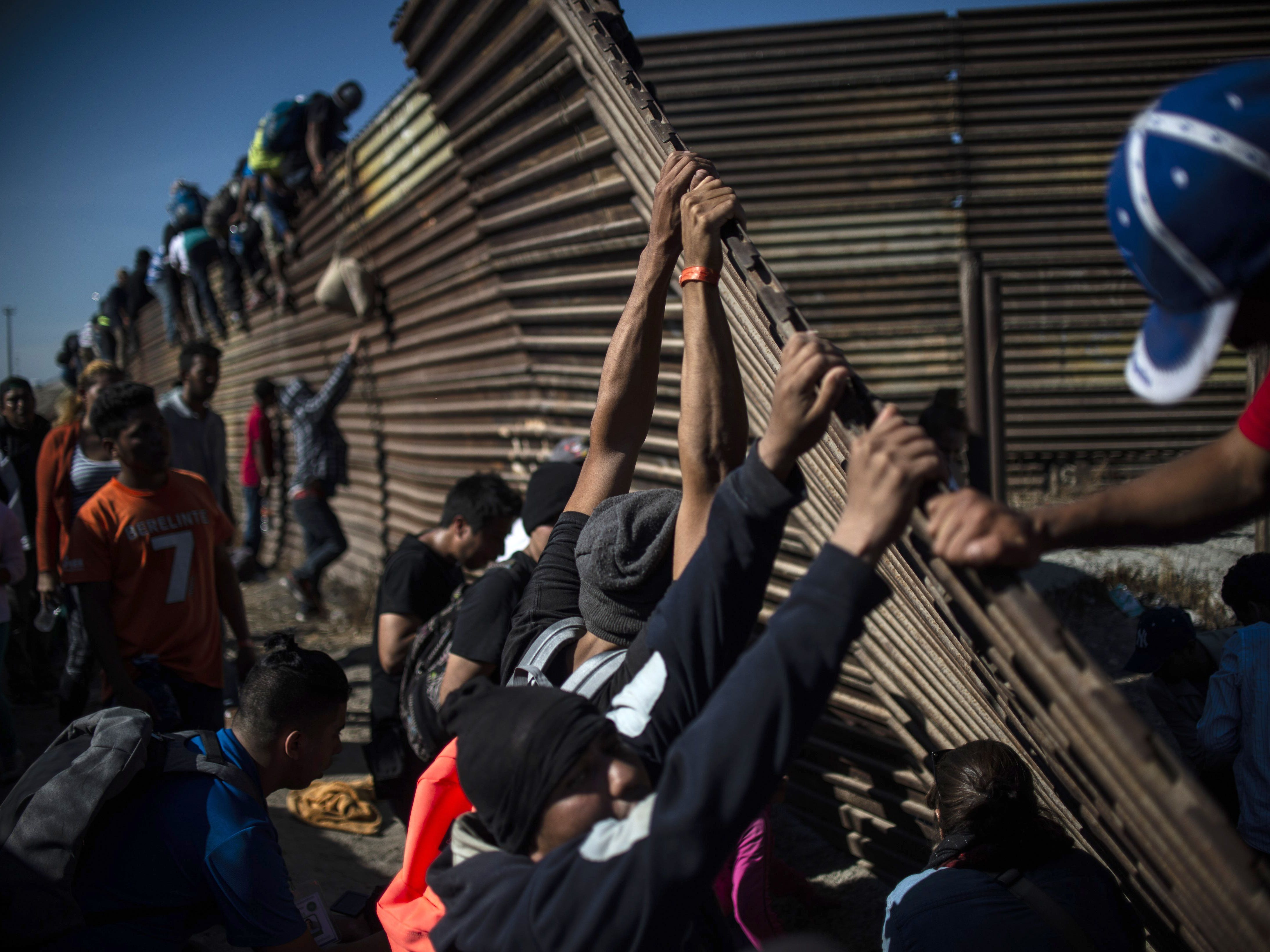A group of Central American migrants climb the border fence between Mexico and the United States as others try to bring it down, near El Chaparral border crossing, in Tijuana, Baja California State, Mexico, on Nov. 25, 2018.