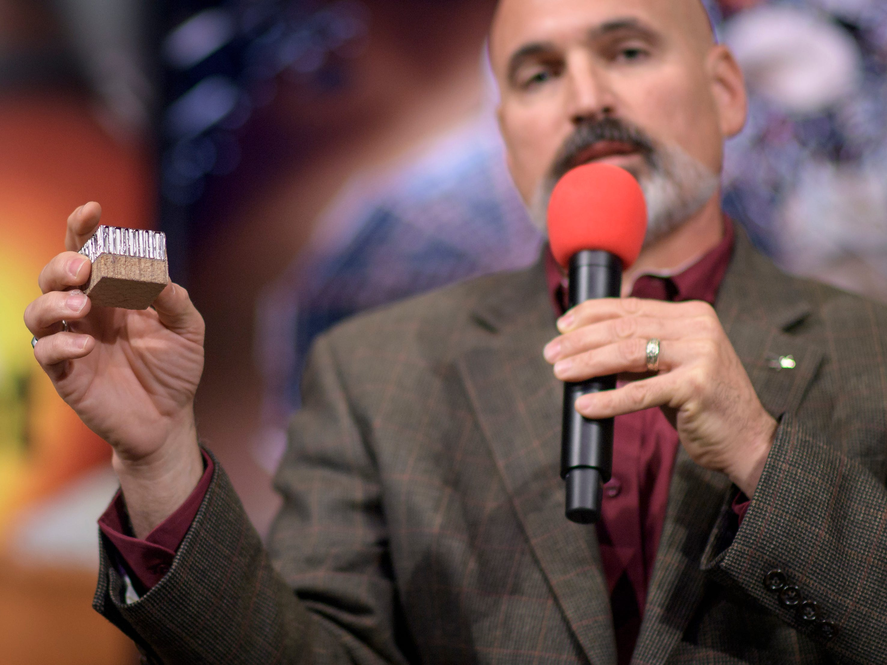 Tim Priser, quality director at Lockheed Martin Space Systems, shows a small piece of the type of heat shield used on the Mars InSight, during a social media briefing Sunday, Nov. 25, 2018, at NASA's Jet Propulsion Laboratory in Pasadena, Calif.