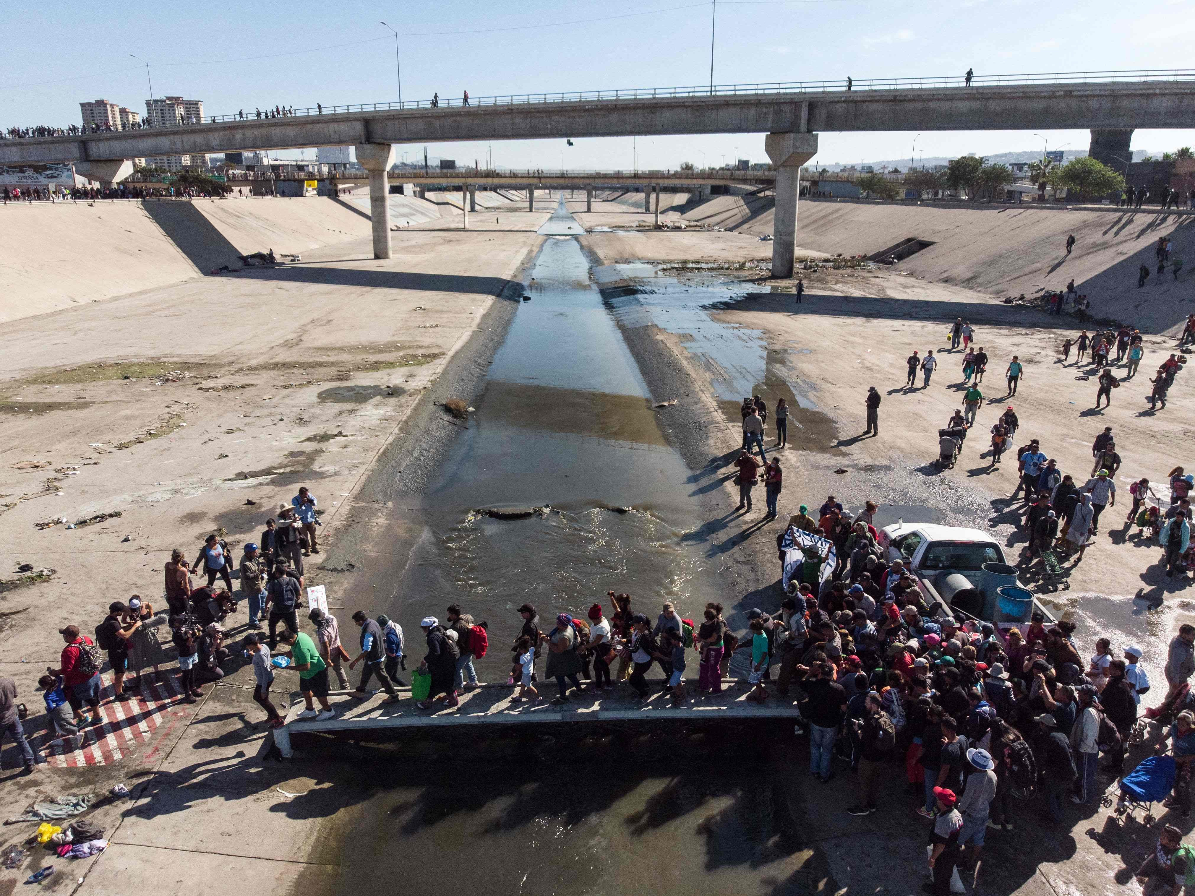 A group of Central American migrants cross the almost dry riverbed of the Tijuana River in an attempt to get to El Chaparral port of entry, in Tijuana, Mexico, near the U.S.-Mexico border on Nov. 25, 2018.