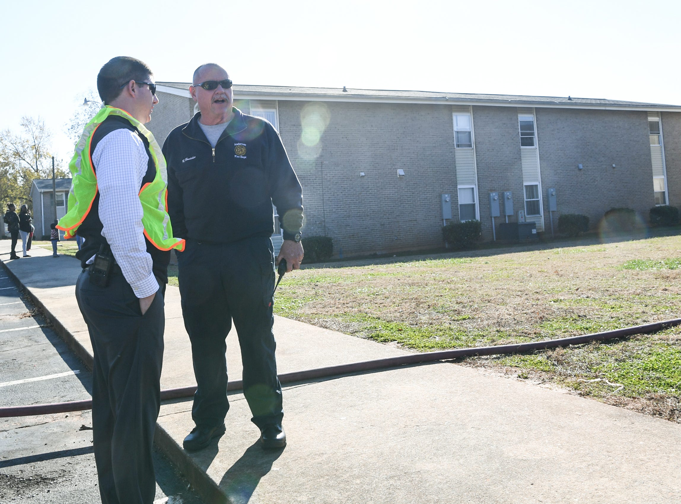 David McCuen, left, Assistant City Manager, and Fire Chief Randy Bratcher, stand near firemen working at fire in building 8 of the Friendship Court Apartments in Anderson on Tuesday.