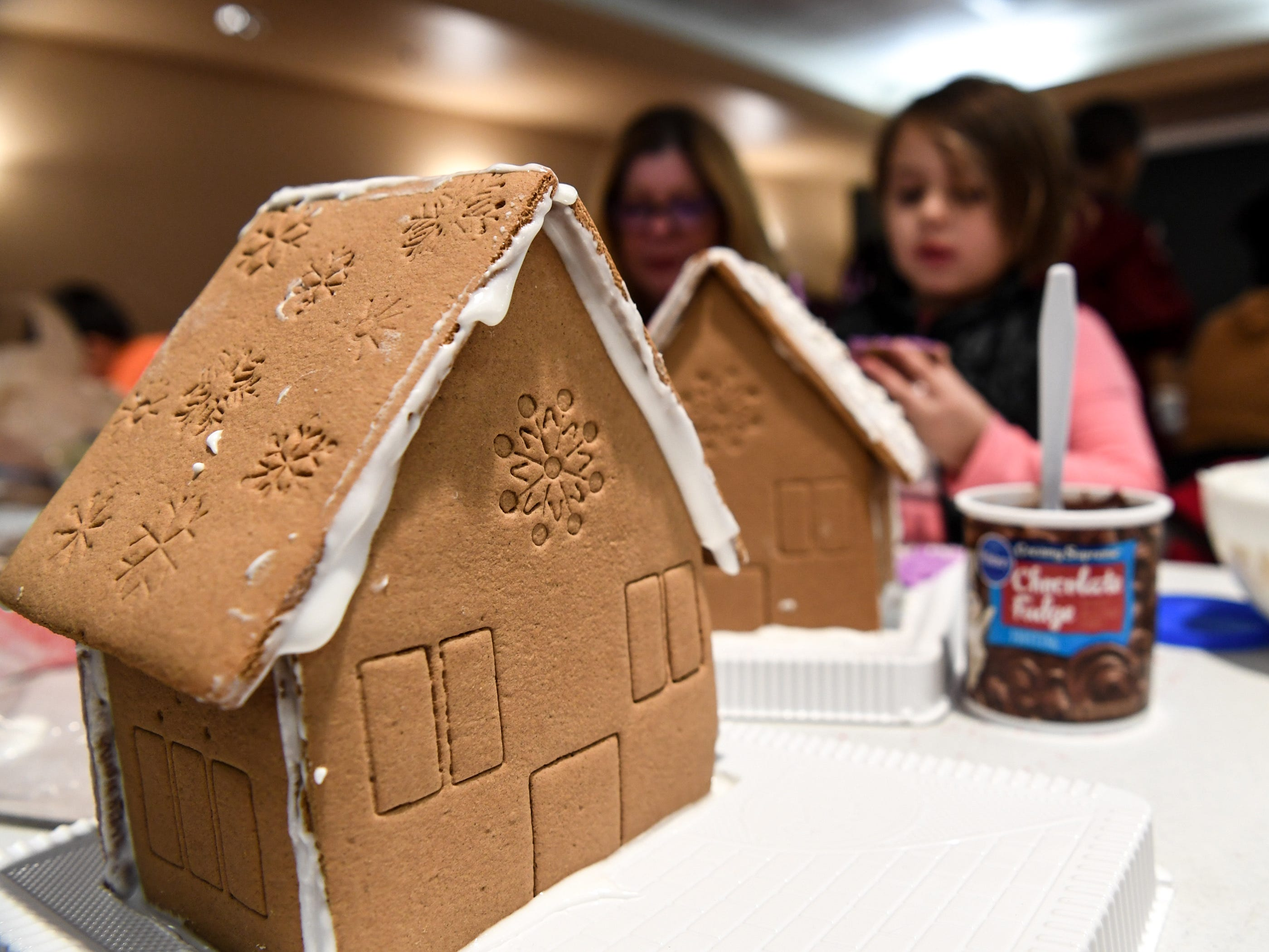 Annabeth Kolb works on a train shaped gingerbread creation during the Big Brothers Big Sisters of the Upstate gingerbread house decorating party at the Anderson County Museum in Anderson on Tuesday. Older mentors spend six hours or more a month with their little brother or sister, including the group activity with materials donated by local businesses. The group matches up mentors in Anderson, Oconee, and Pickens Counties.