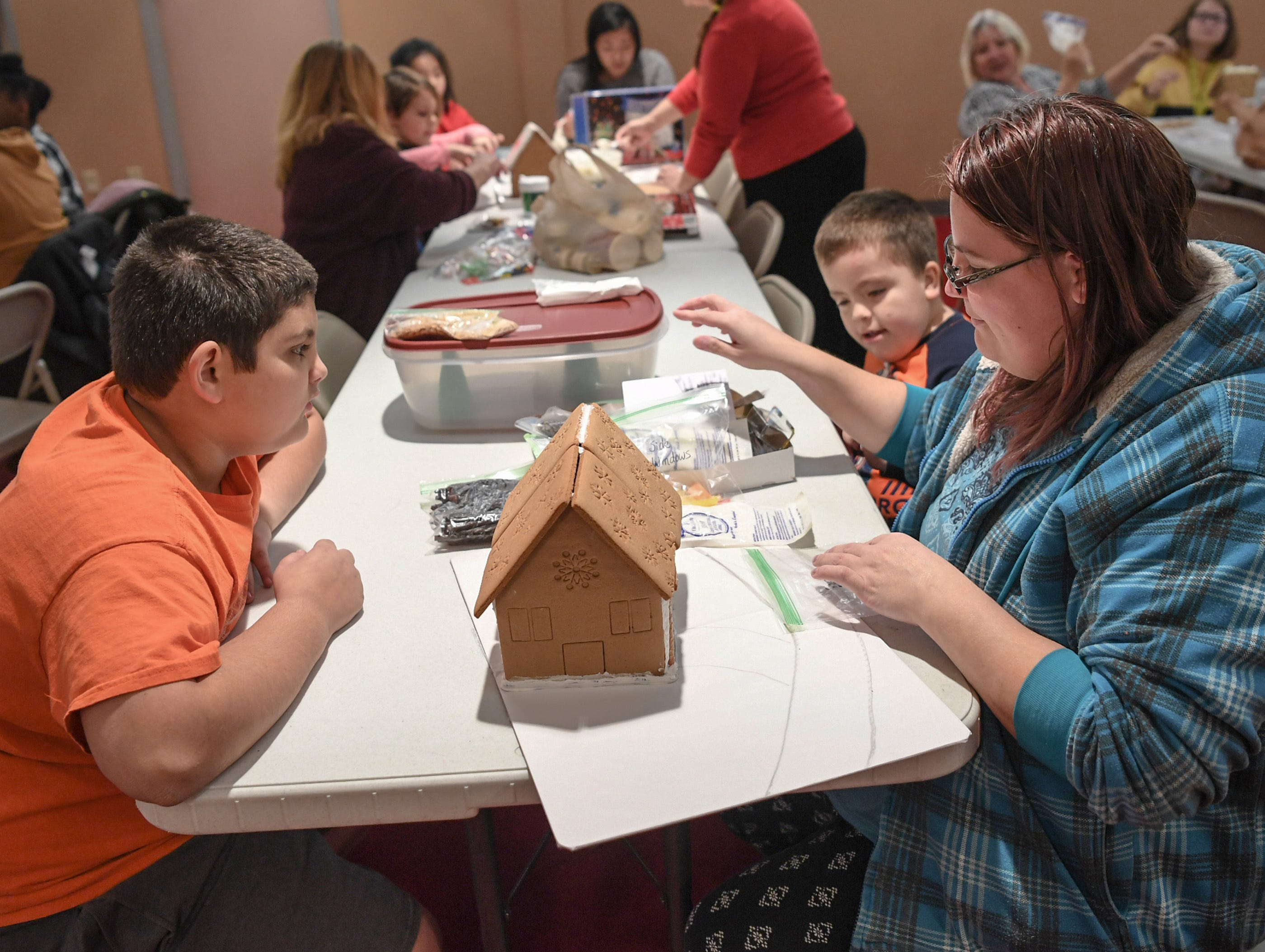 Rafael Martinez, left, and Doris Lehman make a gingerbread house in the shape of a train during the Big Brothers Big Sisters of the Upstate gingerbread house decorating party at the Anderson County Museum in Anderson on Tuesday.