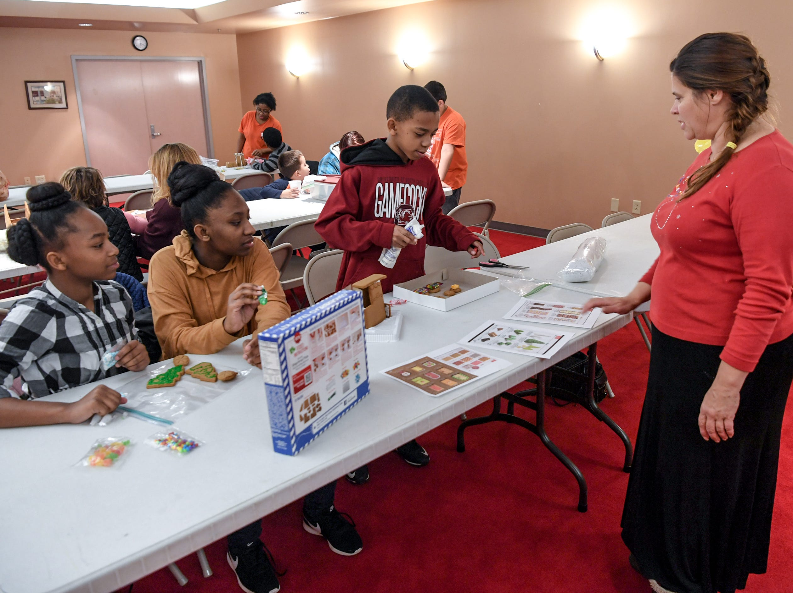 Carrie Kolb, right, a program specialist for Big Brothers Big Sisters of the Upstate, works with Tamara Finley, left, Breanna Finley, and Branddon Finley getting started during a gingerbread house decorating party at the Anderson County Museum in Anderson on Tuesday.