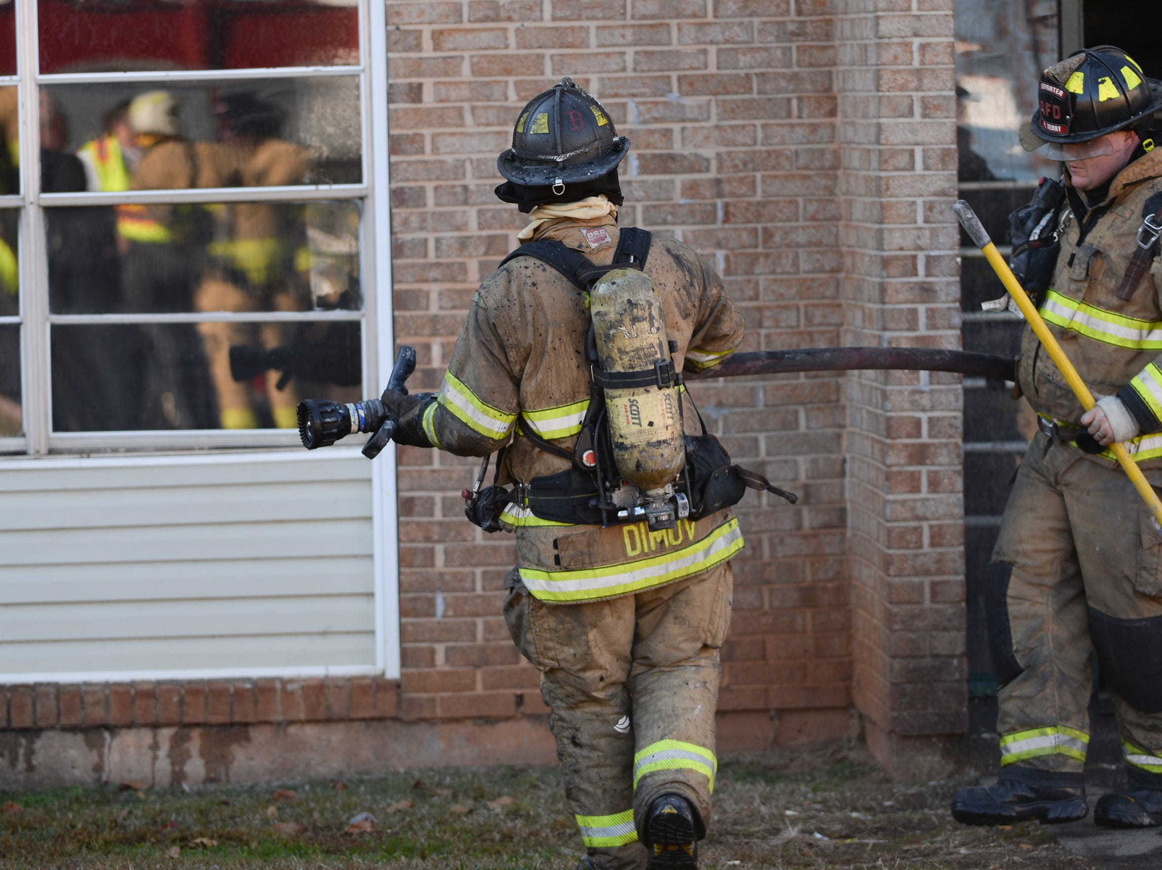 Anderson firemen work at the fire in building 8 of the Friendship Court Apartments in Anderson on Tuesday.