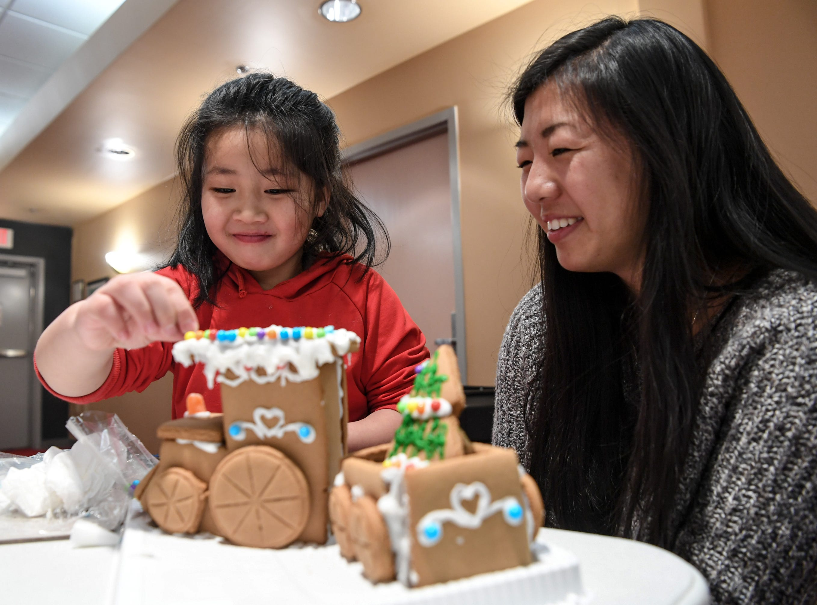 Nicole Lin, left, of Anderson smiles with Emily Claypool, right, while making their own train shaped gingerbread creation, during the Big Brothers Big Sisters of the Upstate gingerbread house decorating party at the Anderson County Museum in Anderson on Tuesday. Older mentors spend six hours or more a month with their little brother or sister, including the group activity with materials donated by local businesses. The group matches up mentors in Anderson, Oconee, and Pickens Counties.